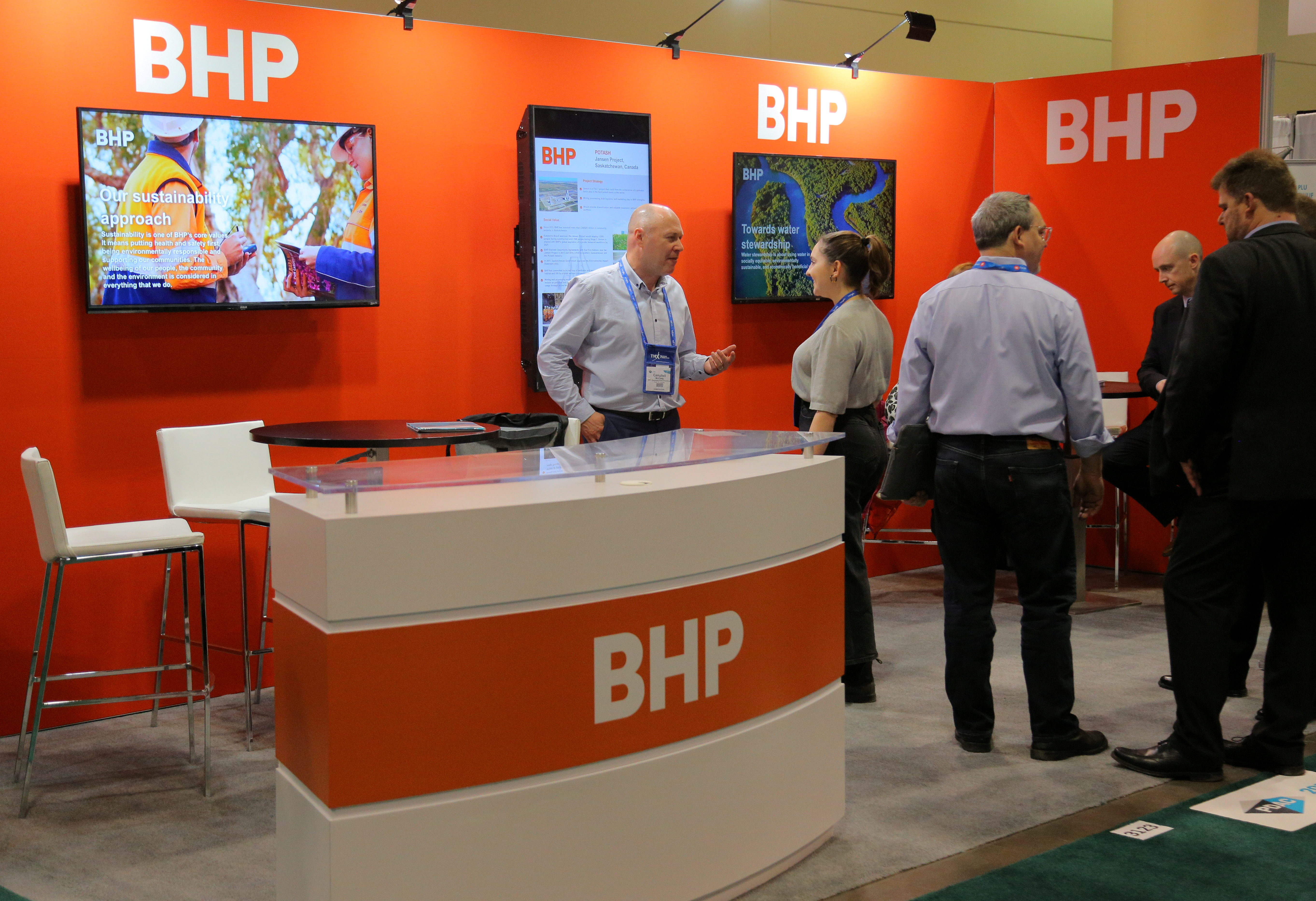 Visitors to the BHP (formerly known as BHP Billiton) booth speak with representatives during the Prospectors and Developers Association of Canada (PDAC) annual convention in Toronto, Ontario, Canada March 4, 2019. REUTERS/Chris Helgren/File Photo