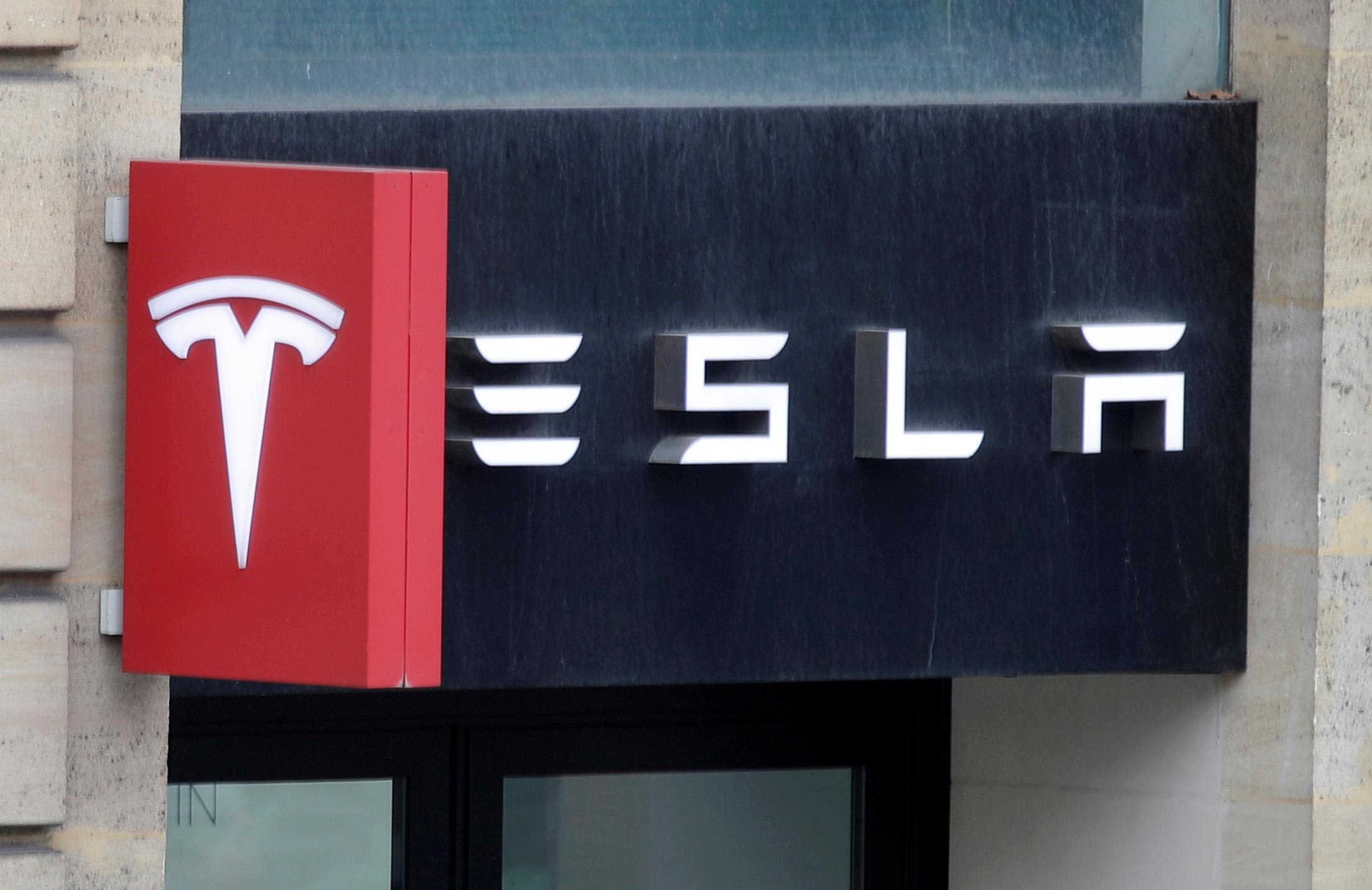 The logo of Tesla is seen on a store in Paris, France, October 30, 2020. REUTERS/Charles Platiau