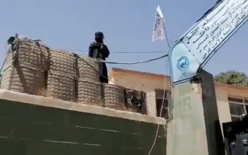 A fighter stands guard next to a Taliban flag raised at the gates outside the police headquarters, in city of Ghazni, Afghanistan in this screen grab taken from a video released by the Taliban on August 12, 2021. Taliban Handout/via REUTERS