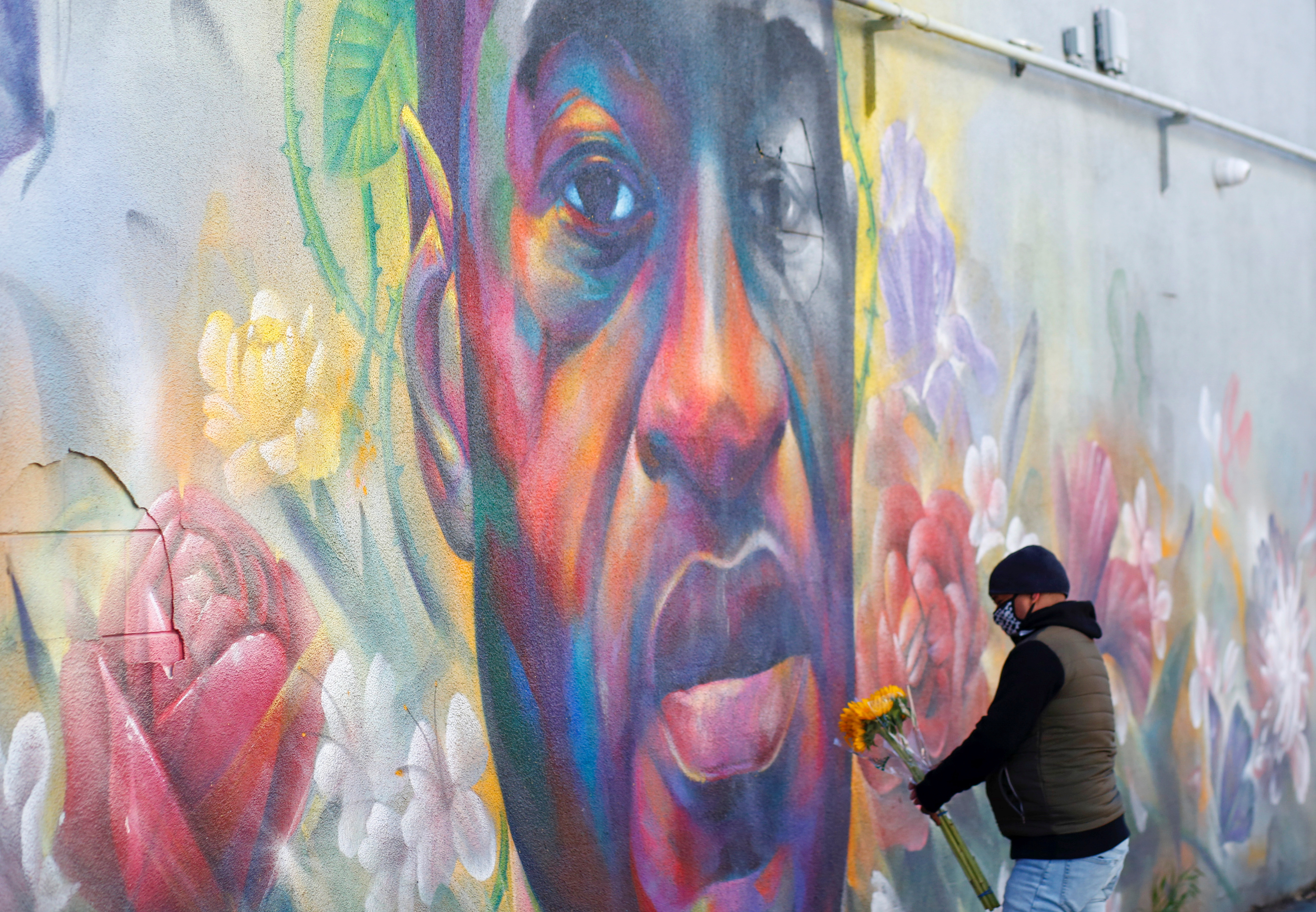 A man places flowers at a mural of George Floyd after the verdict in the trial of former Minneapolis police officer Derek Chauvin, found guilty of the death of Floyd, in Denver, Colorado, U.S., April 20, 2021. REUTERS/Kevin Mohatt
