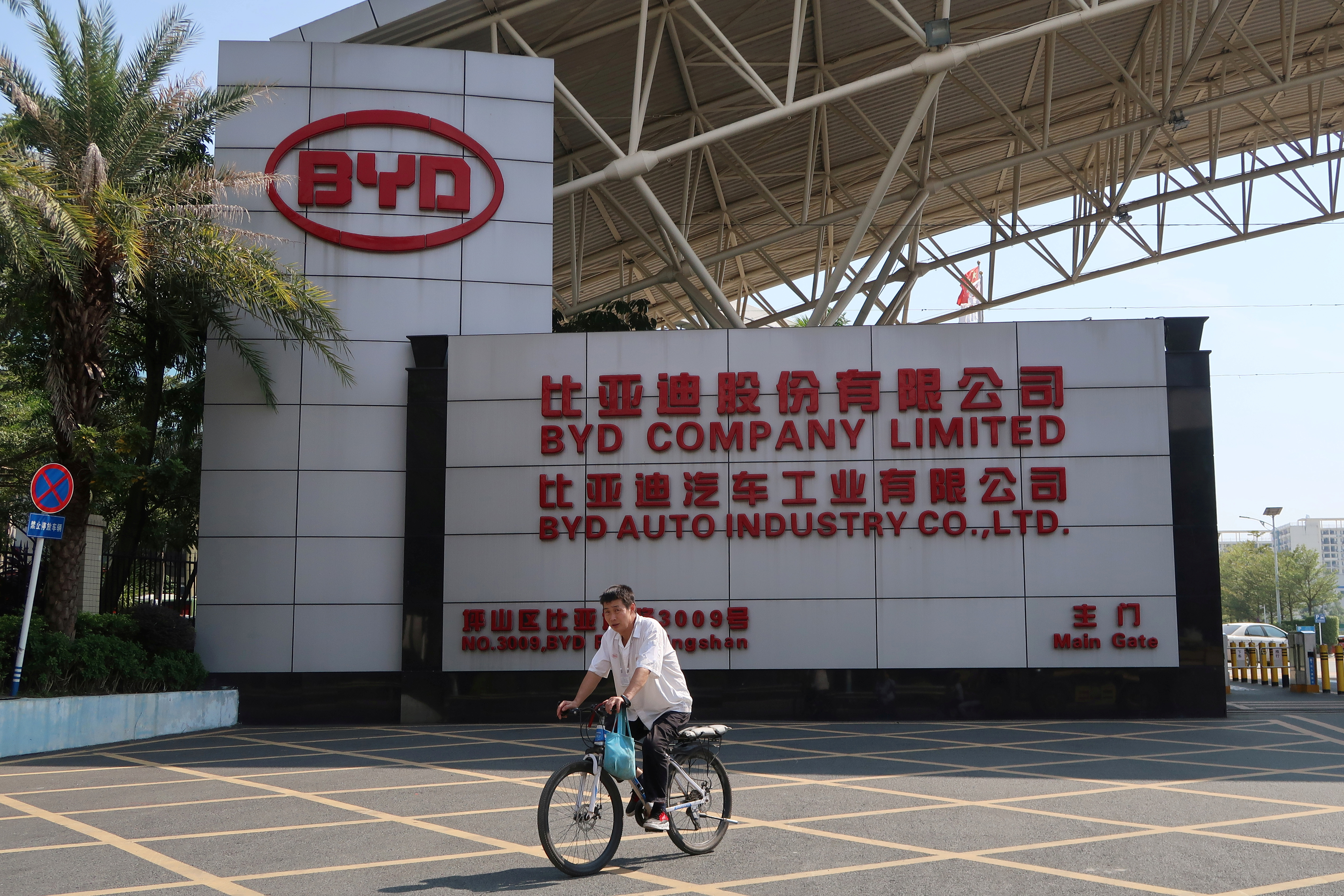 A man cycles past an entrance to the headquarters of Chinese electric car maker BYD in Shenzhen's Pingshan district, Guangdong province, China October 25, 2019. REUTERS/Yilei Sun/File Photo