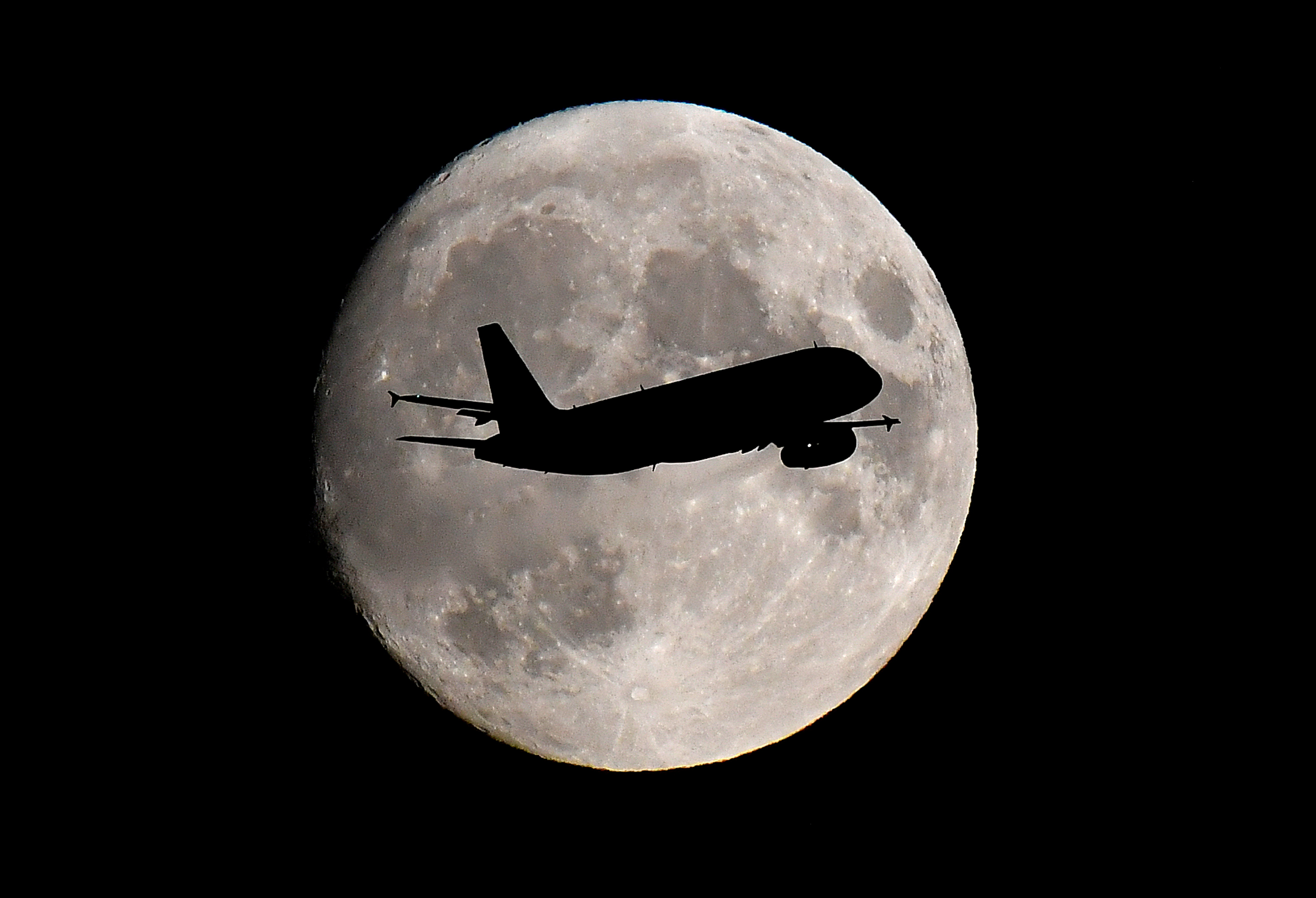A passenger plane passes in front of the moon as it makes its final landing approach to Heathrow Airport in London, Britain September 12, 2019. REUTERS/Toby Melville