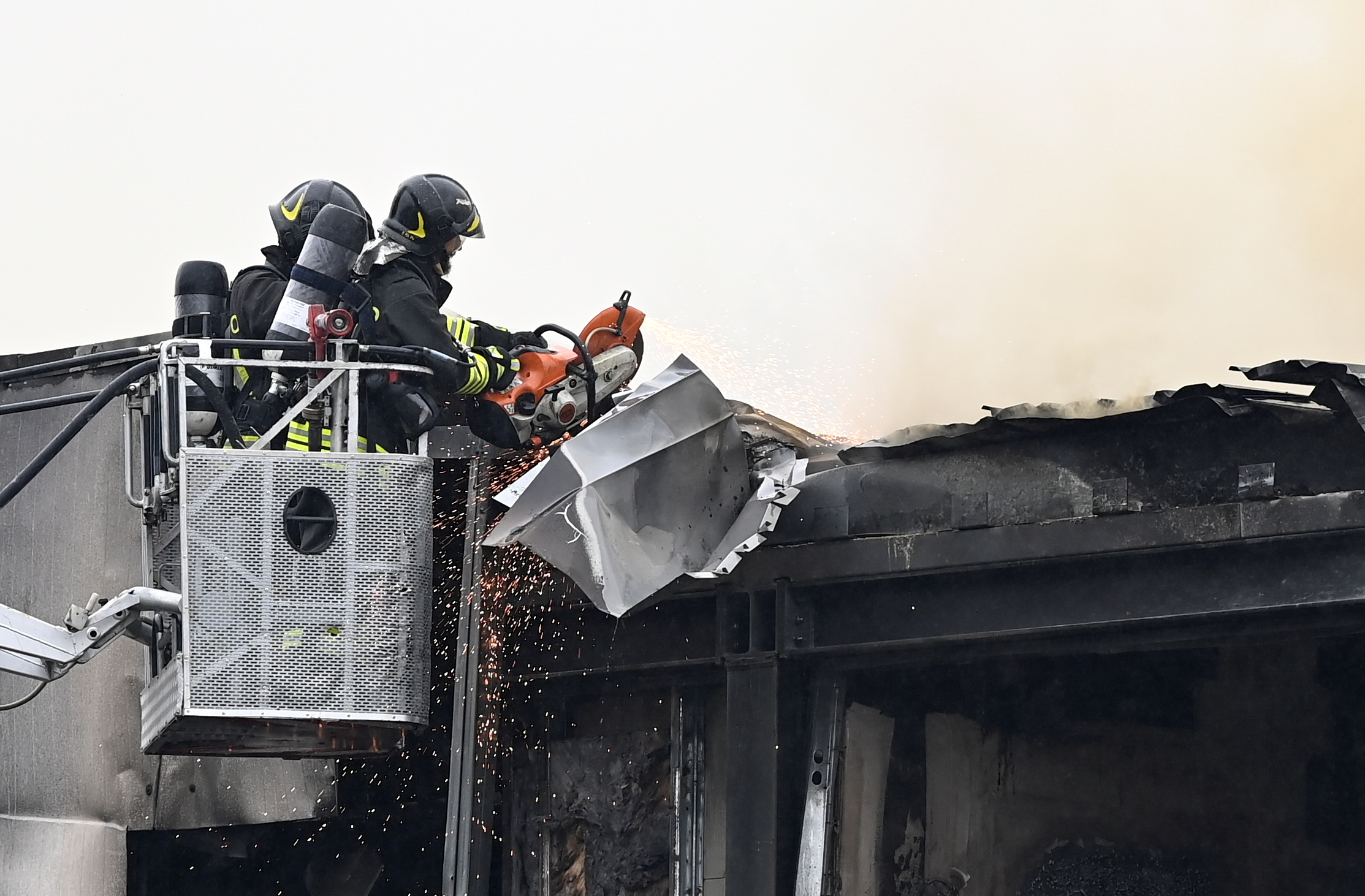 Fire fighters work at the scene where a small plane crashed into a building in San Donato Milanese, Italy, October 3, 2021. REUTERS/Flavio Lo Scalzo