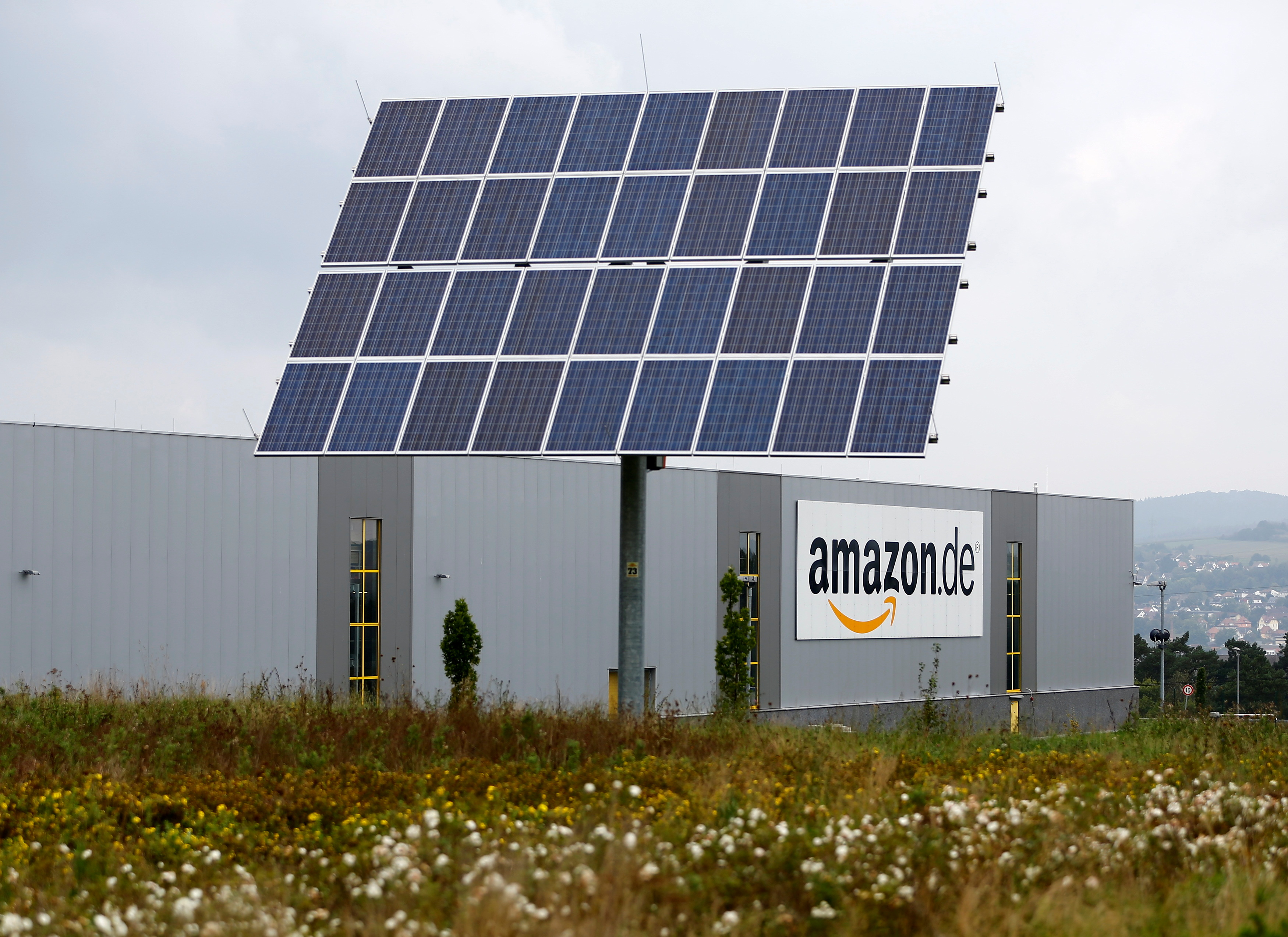 Photovoltaic panels stand in front of the Amazon distribution centre in Bad Hersfeld September 22, 2014. REUTERS/Kai Pfaffenbach/File Photo