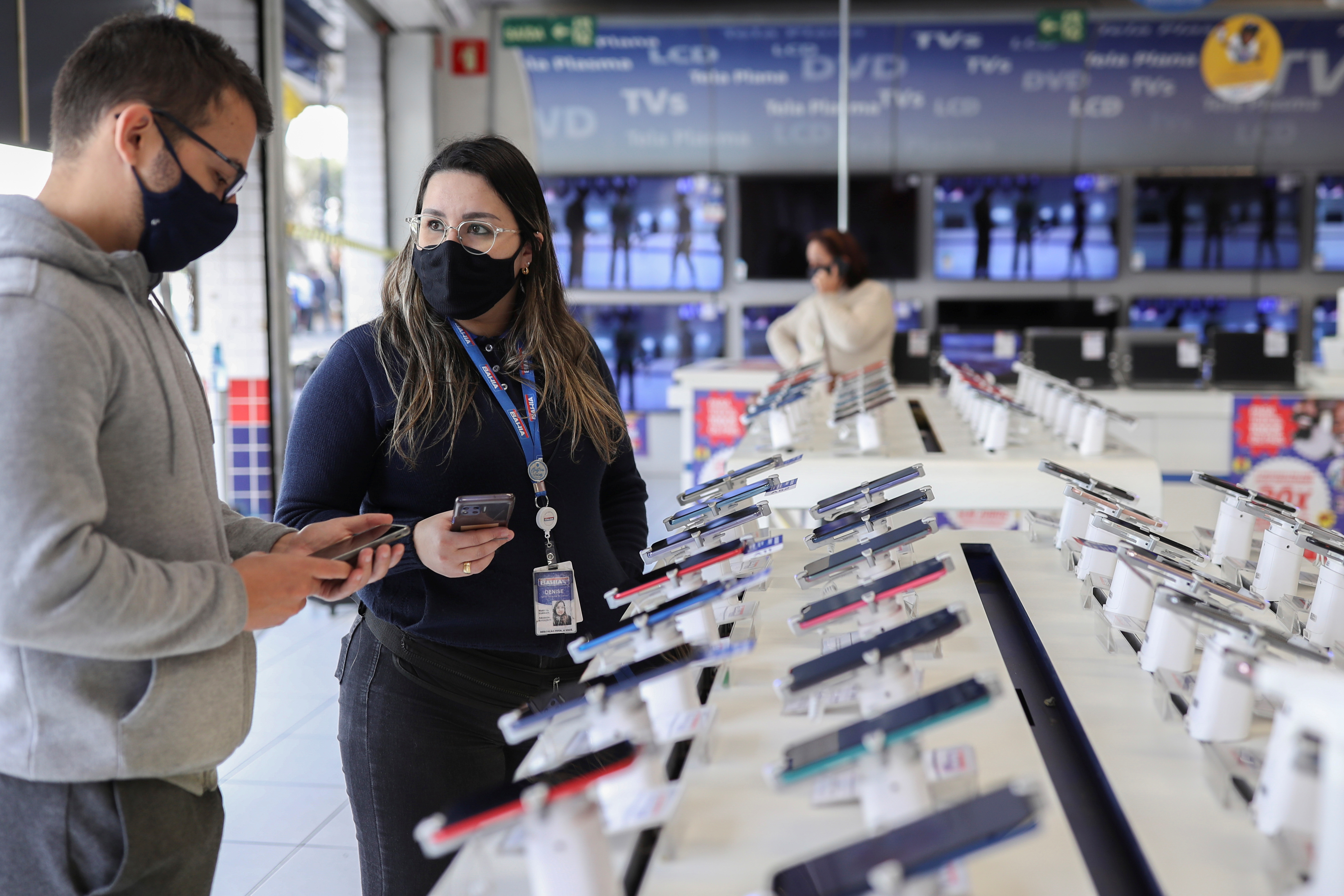 Vendor Denise Fernandes de Queiroz talks to a costumer as they enter a messaging app on their phones at a Casas Bahia store in Sao Paulo, Brazil, August 3, 2021. Picture taken August 3, 2021. REUTERS/Amanda Perobelli