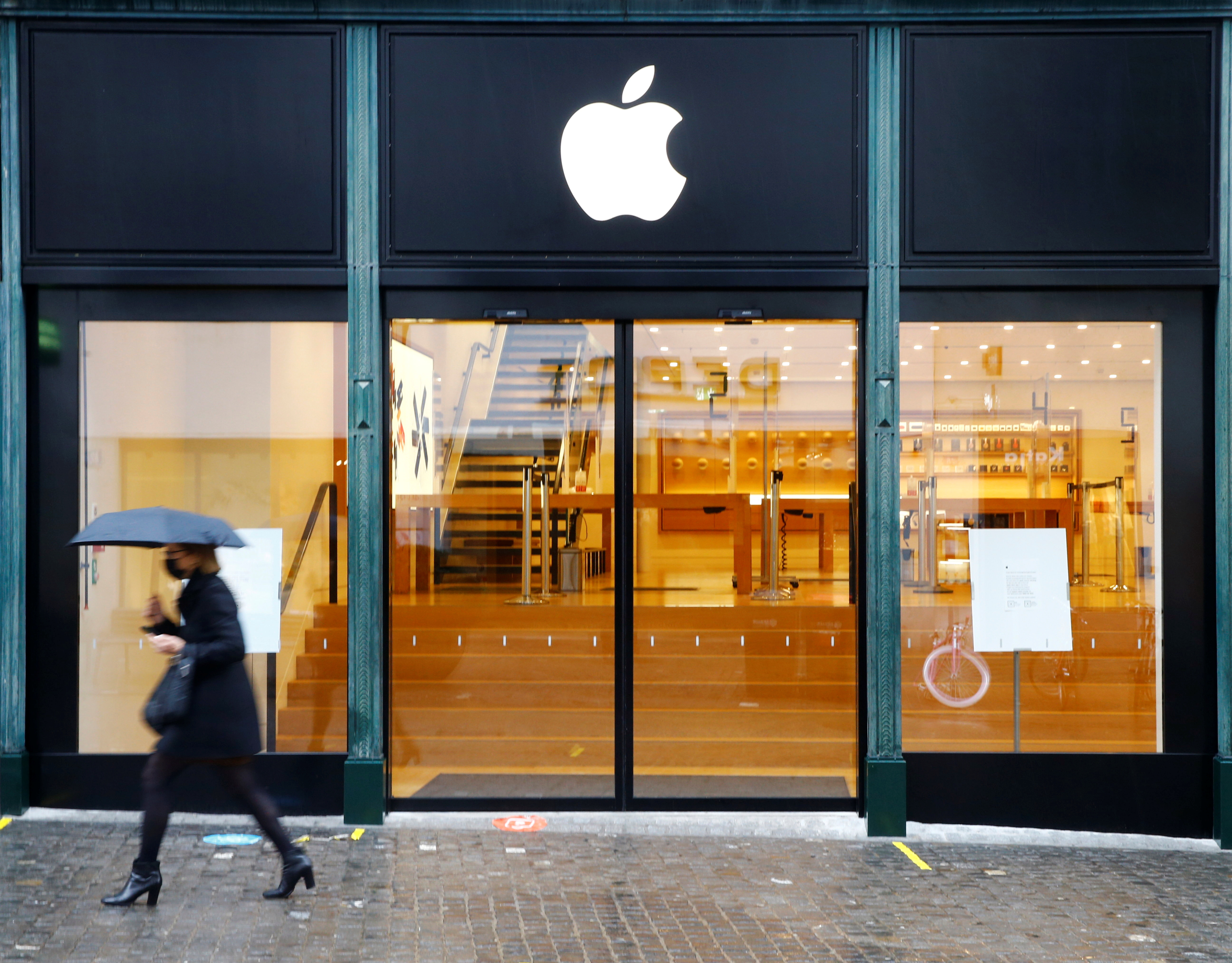 A person walks past an Apple store, which is closed during a partial lockdown, as the spread of the coronavirus disease (COVID-19) continues, in Zurich, Switzerland January 28, 2021. REUTERS/Arnd Wiegmann
