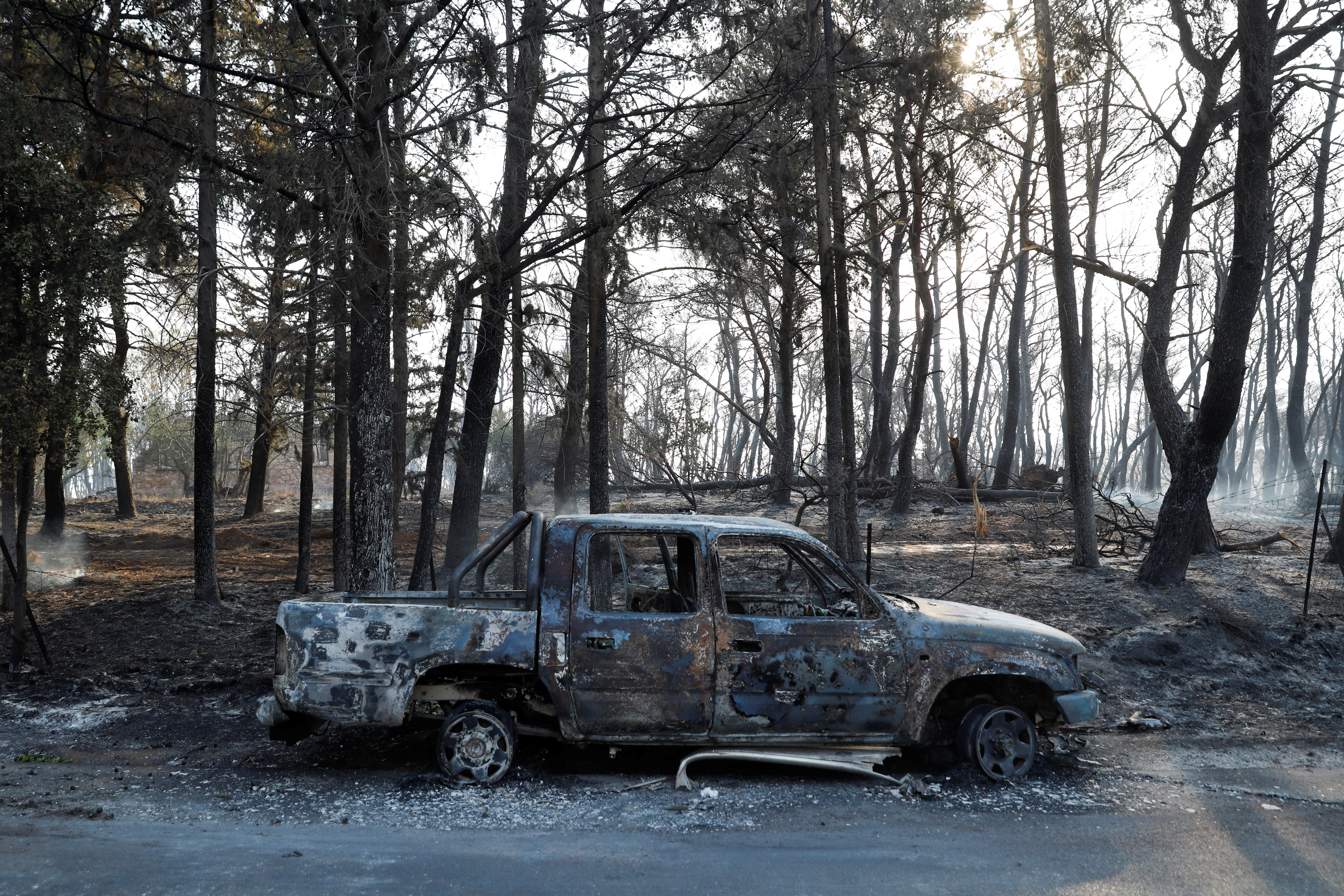 A burnt car is seen as a wildfire continues to rage in Varympompi suburb, north of Athens, Greece, August 4, 2021. REUTERS/Costas Baltas