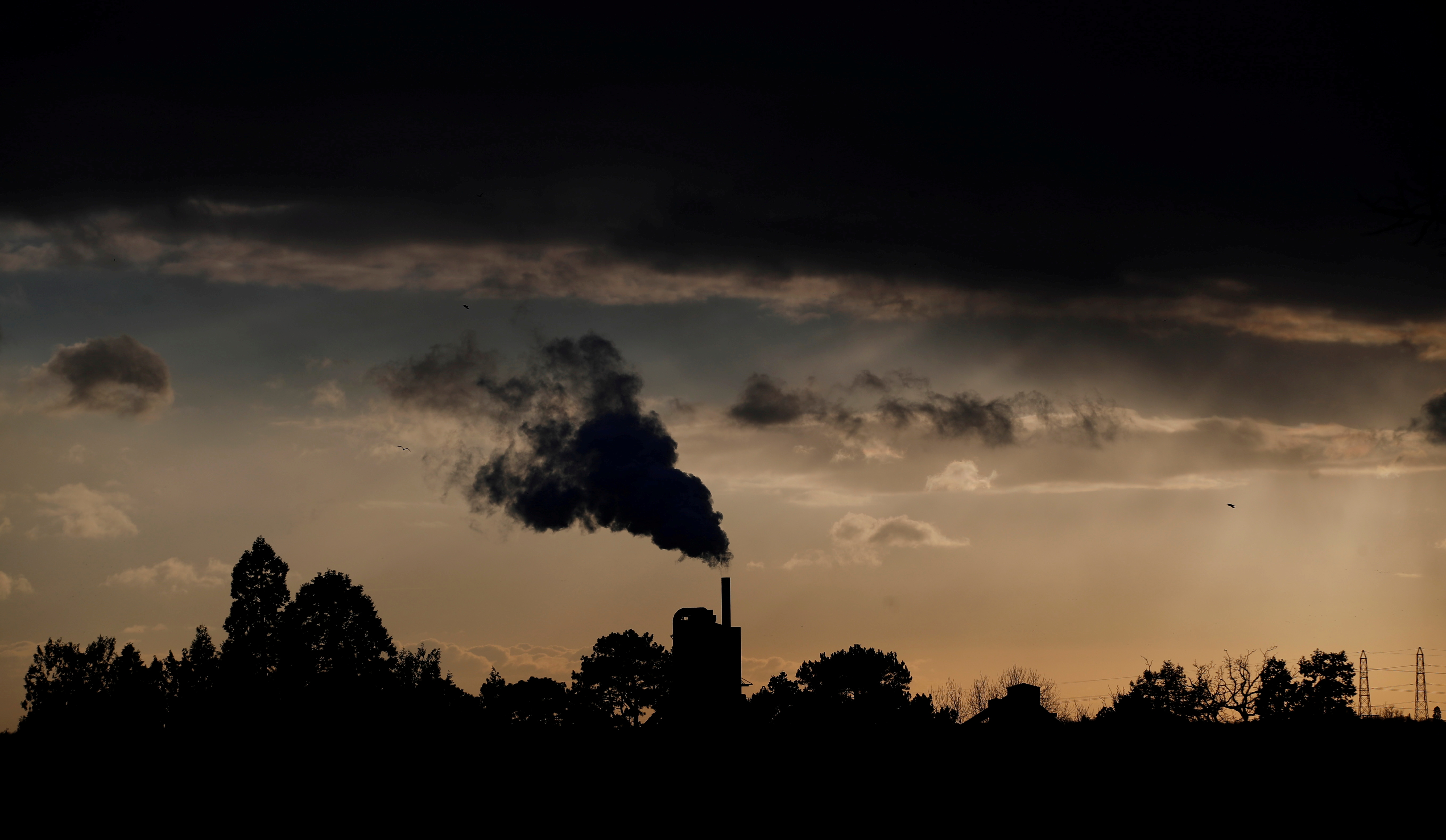 Smoke rises above a factory at sunset in Rugby, Britain February 10, 2021. REUTERS/Matthew Childs/File Photo