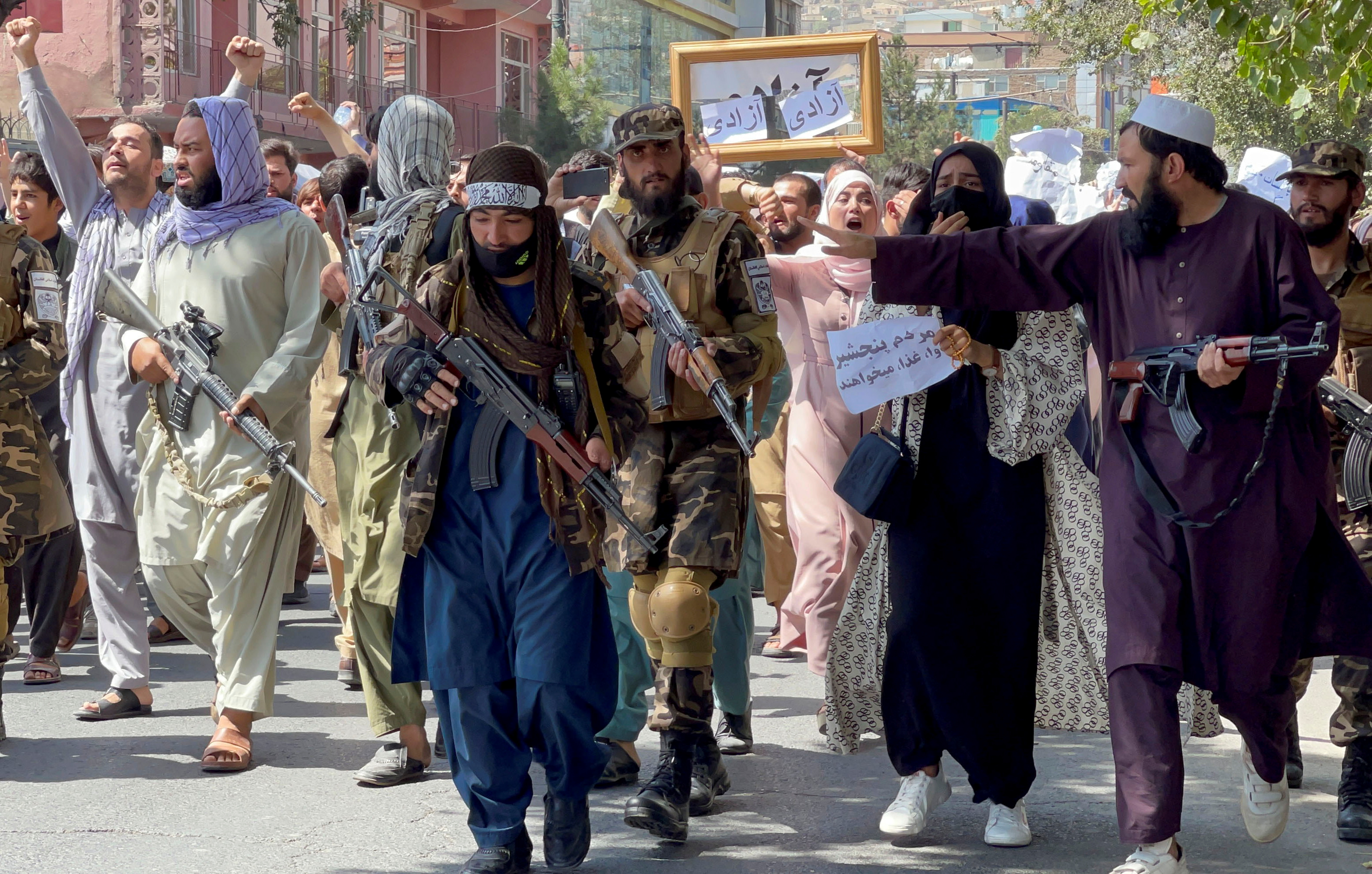Taliban forces walk in front of Afghan demonstrators as they shout slogans during an anti-Pakistan protest, near the Pakistan embassy in Kabul, Afghanistan, September 7, 2021. REUTERS/Stringer