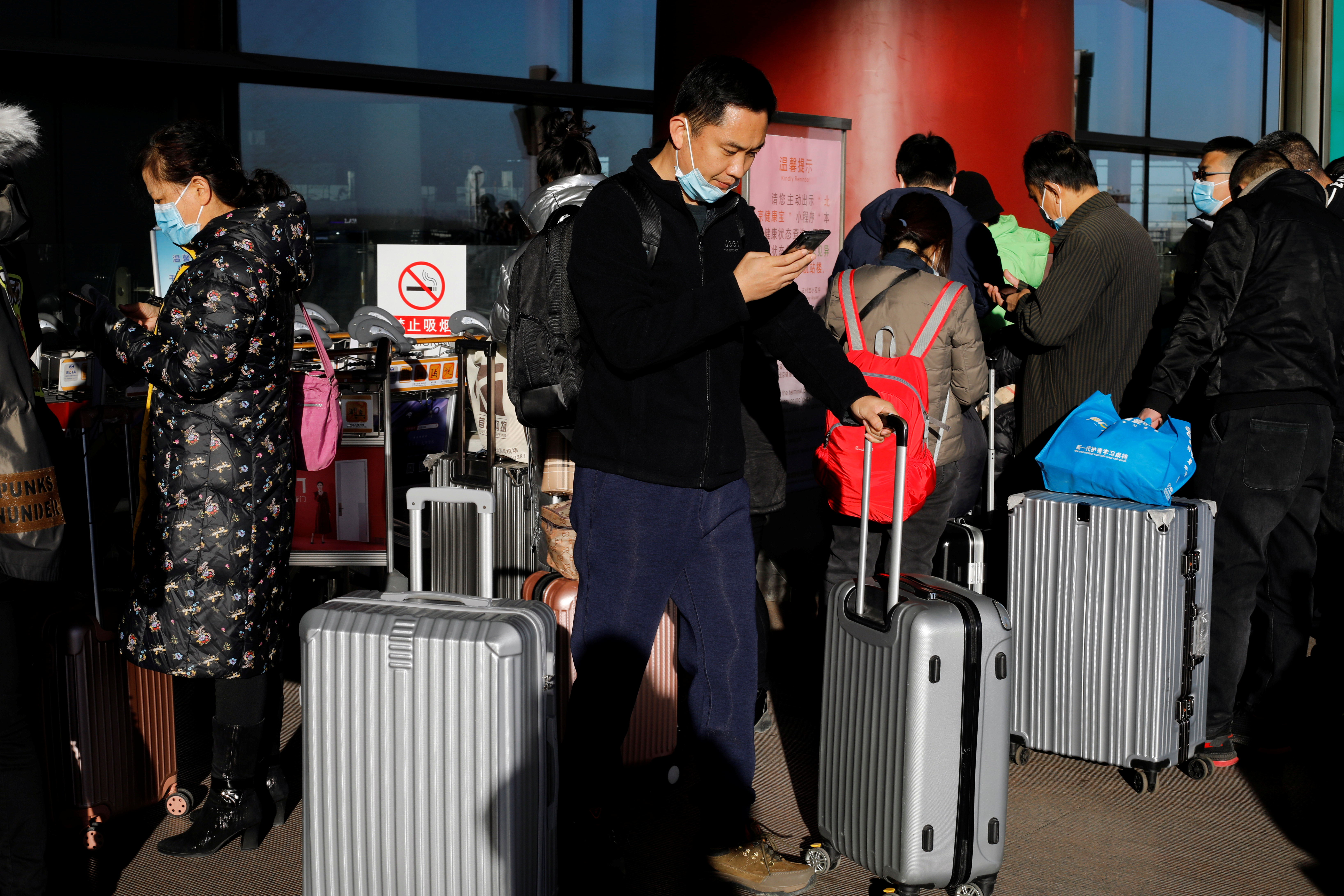 Travellers arrive with their luggage at the Beijing Capital International Airport following the coronavirus disease (COVID-19) outbreak in Beijing, China December 30, 2020. REUTERS/Tingshu Wang