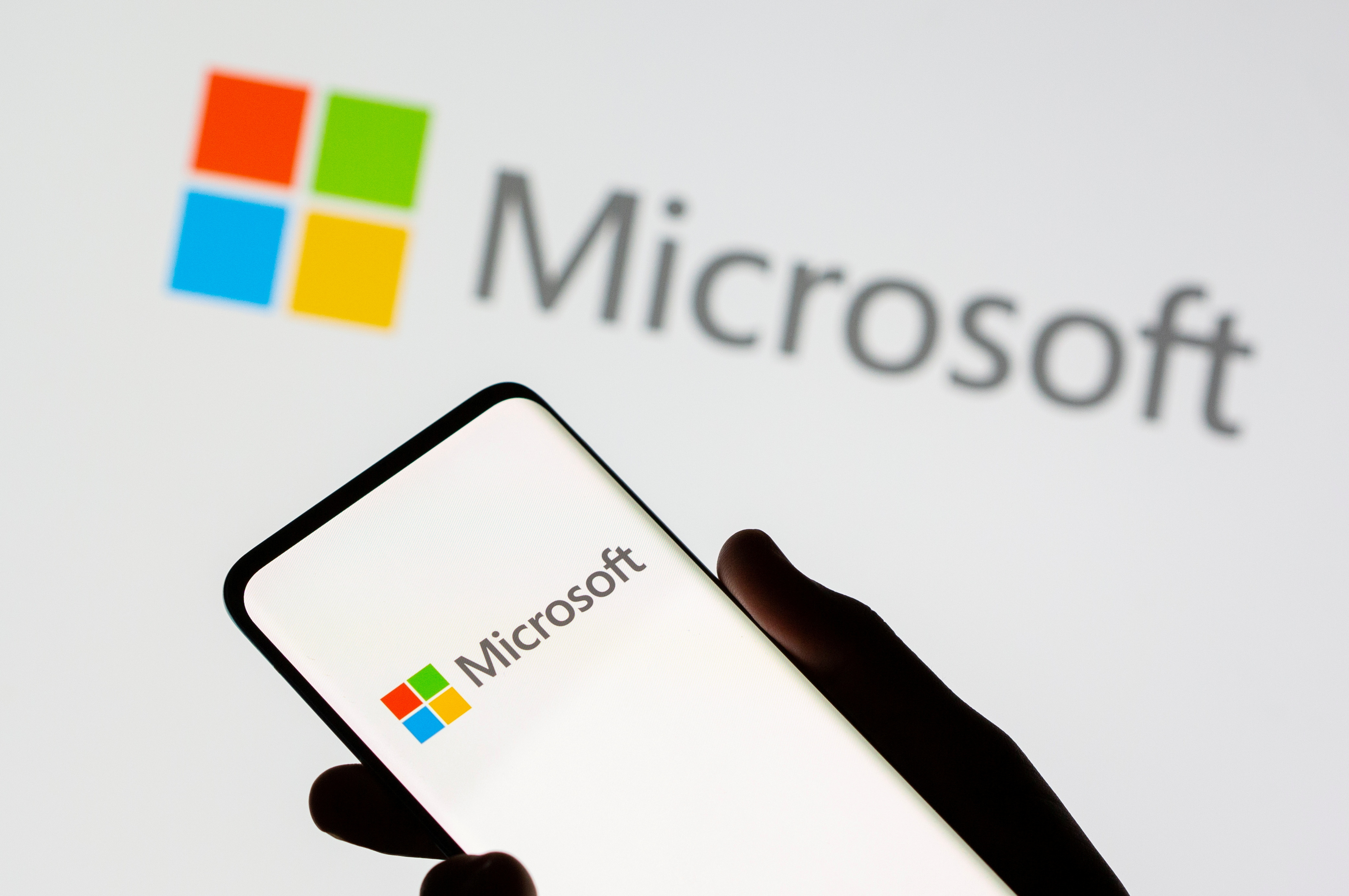 A smartphone is seen in front of a Microsoft logo displayed in this illustration taken, July 26, 2021. REUTERS/Dado Ruvic/Illustration/File Photo