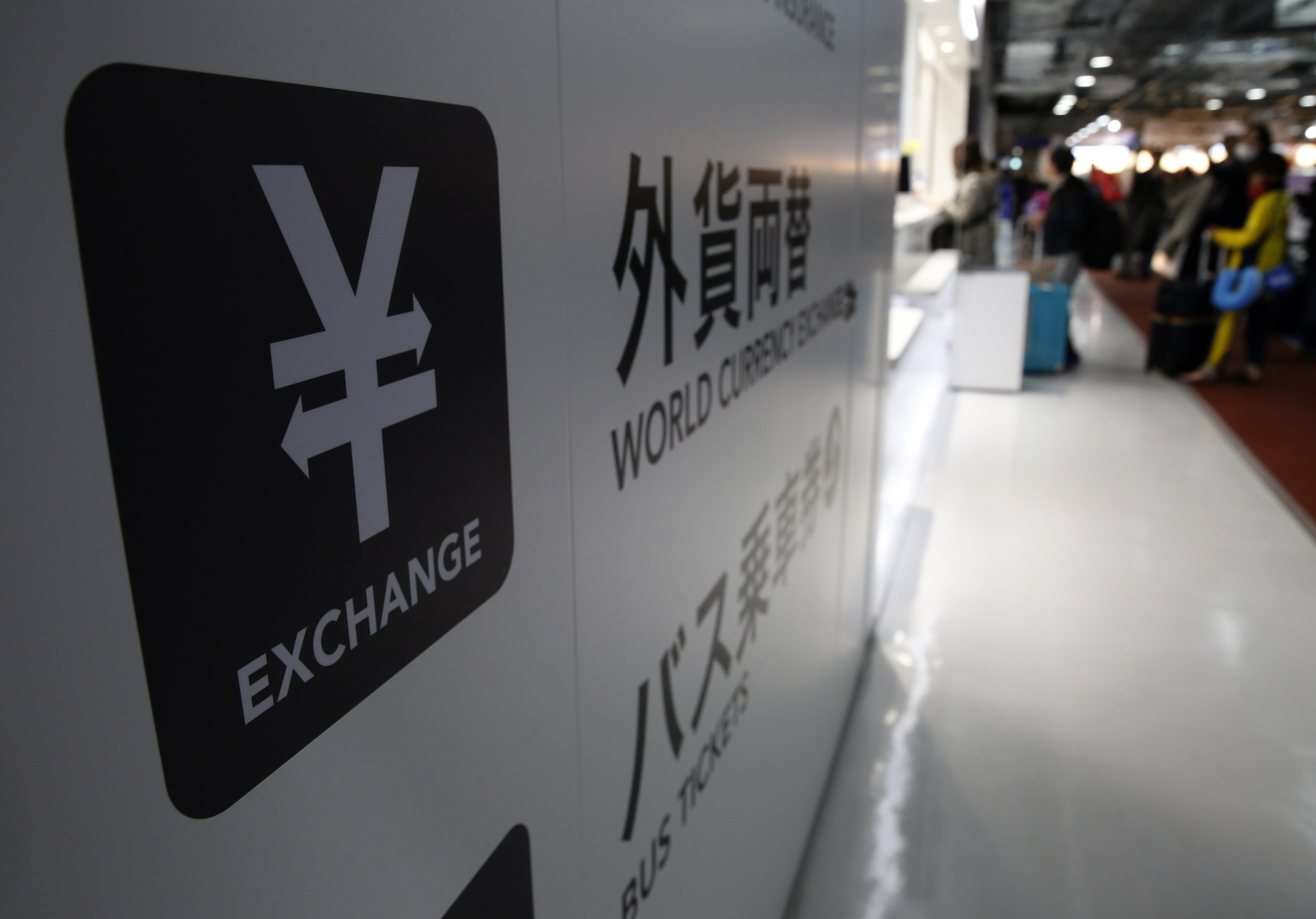 A Japanese Yen currency sign (L) is seen at a currency exchange office as people line up to exchange money at Narita International airport, near Tokyo, Japan, March 25, 2016. The dollar was on track on Friday for a weekly gain of over 1 percent against a basket of currencies after a chorus of U.S. Federal Reserve officials signalled more interest rate increases than the market had been pricing in. REUTERS/Yuya Shino