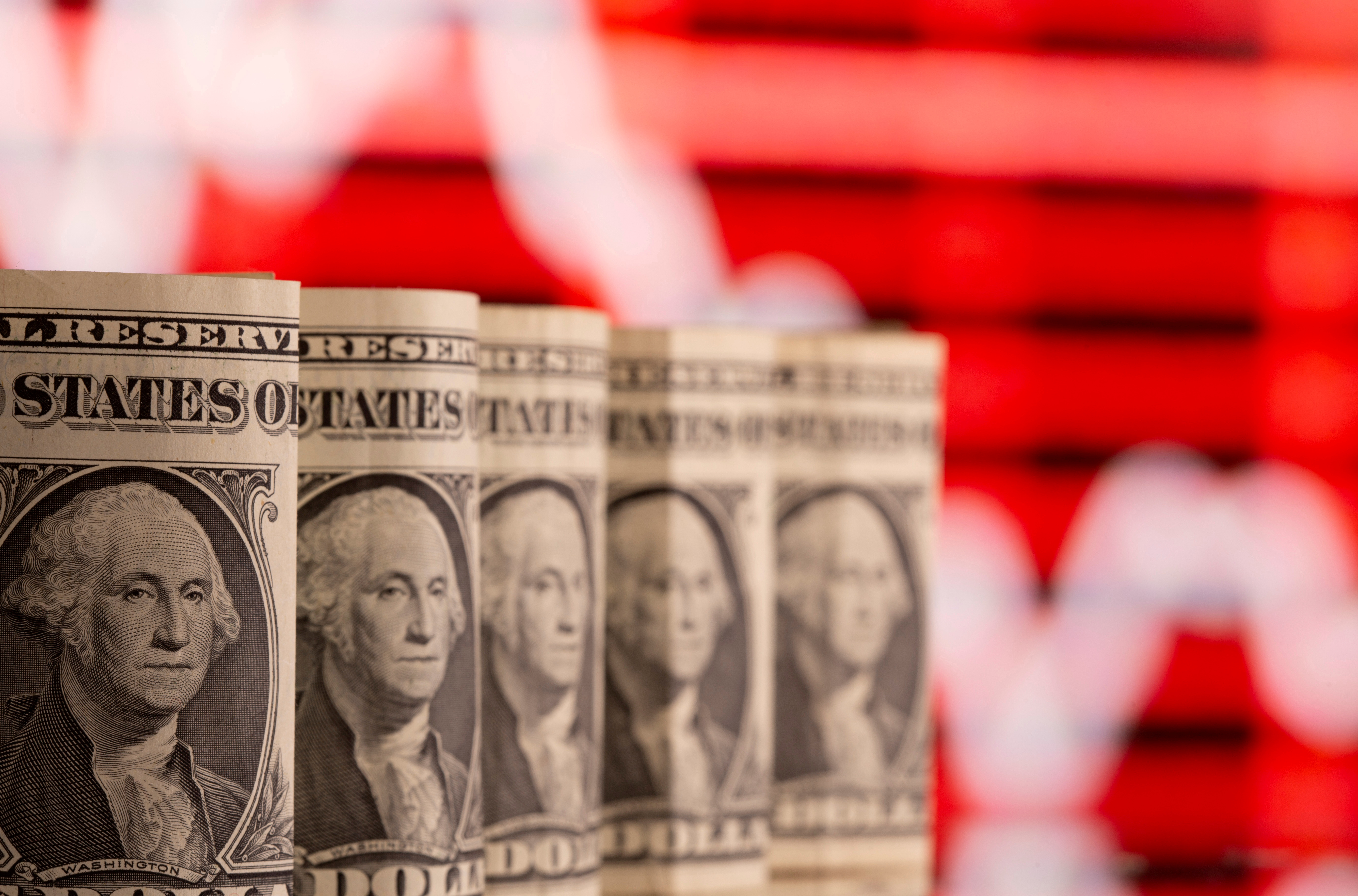 U.S. one dollar banknotes are seen in front of displayed stock graph in this illustration taken February 8, 2021. REUTERS/Dado Ruvic/Illustration/File Photo