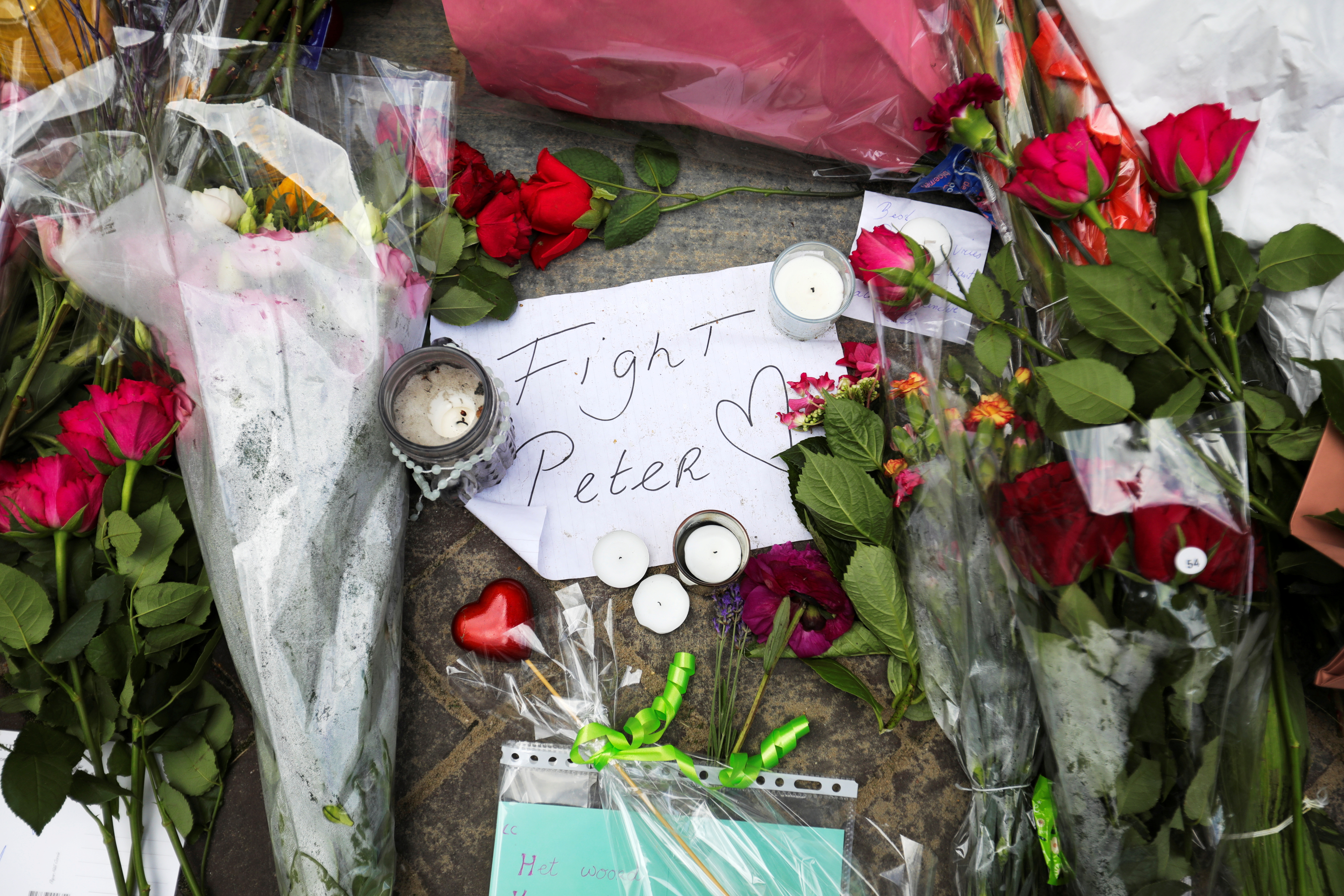 Flowers and a note rest on the place where Dutch celebrity crime reporter Peter R. de Vries has been shot and reported seriously injured in Amsterdam, Netherlands, July 7, 2021. REUTERS/Eva Plevier/File Photo
