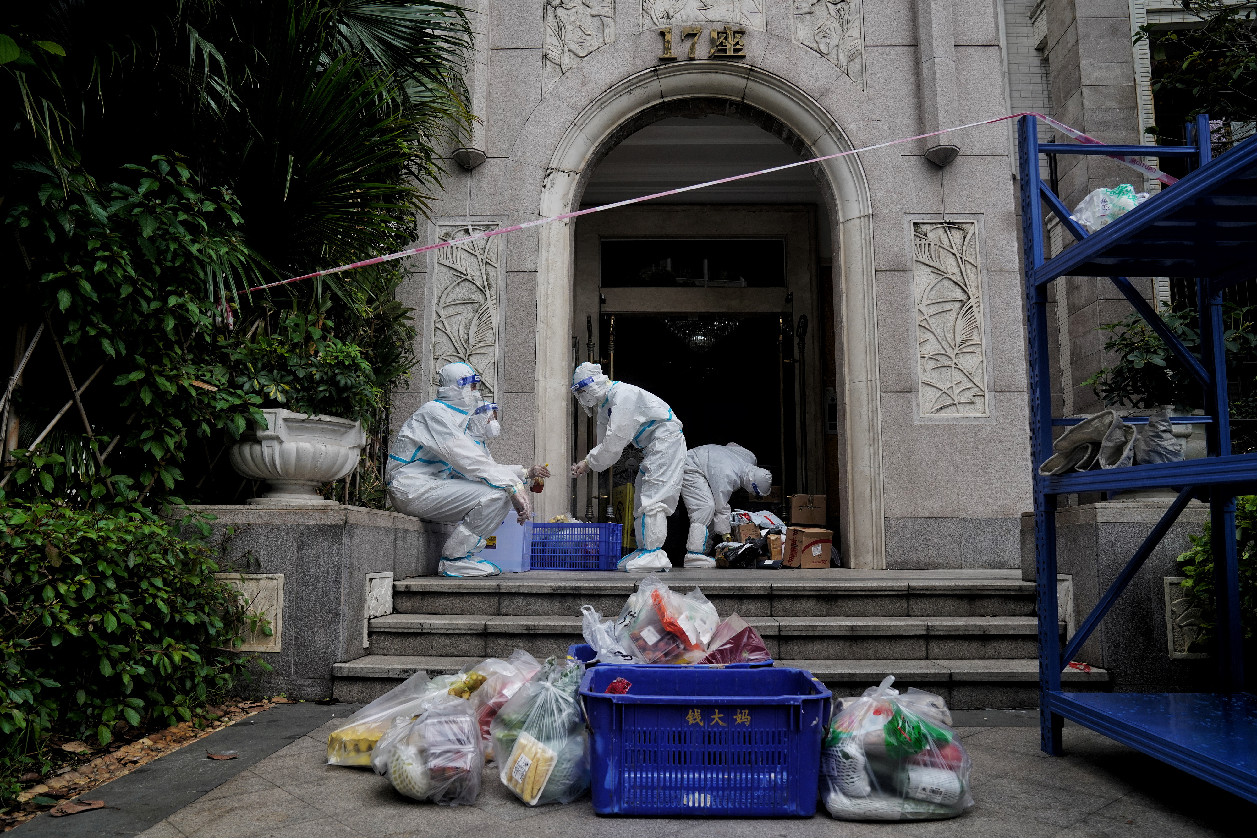Property management workers in protective suits deliver goods to residents at a compound under lockdown due to the recent coronavirus disease (COVID-19) outbreak in Guangzhou, Guangdong province, China June 2, 2021. Picture taken June 2, 2021. China Daily via REUTERS