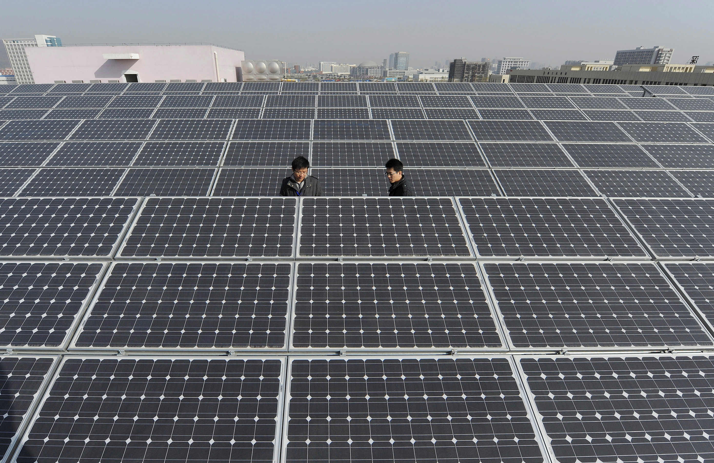 Employees inspect newly-made solar panels on the roof of a Sungrow Power Supply Co., Ltd factory in Hefei, Anhui province December 8, 2010. REUTERS/Stringer