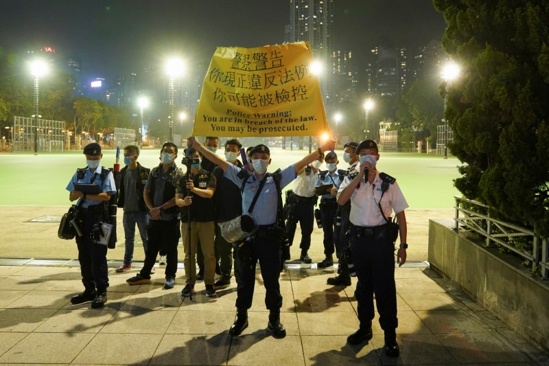 Police officers stand at the entrance to Victoria Park to disperse people mourning at Victoria Park on the 32nd anniversary of the crackdown on pro-democracy demonstrators at Beijing's Tiananmen Square in 1989, in Hong Kong, China June 4, 2021. REUTERS/Lam Yik/File Photo