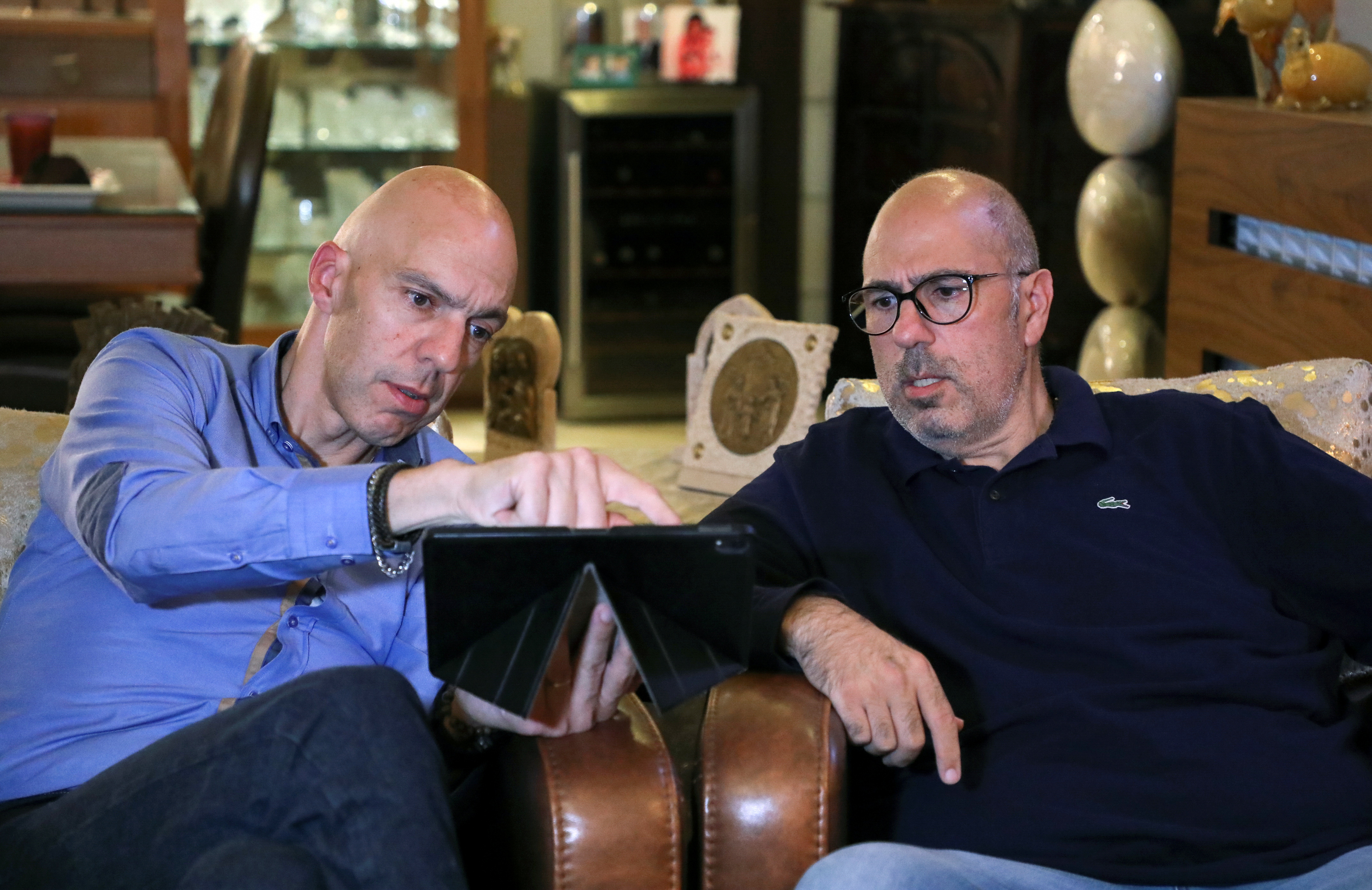 Ralph Khoury, 44, sits with his brother Rony, 49, as they look at a tablet at his home in Qornet El Hamra, Lebanon, September 24, 2021. REUTERS/Mohamed Azakir