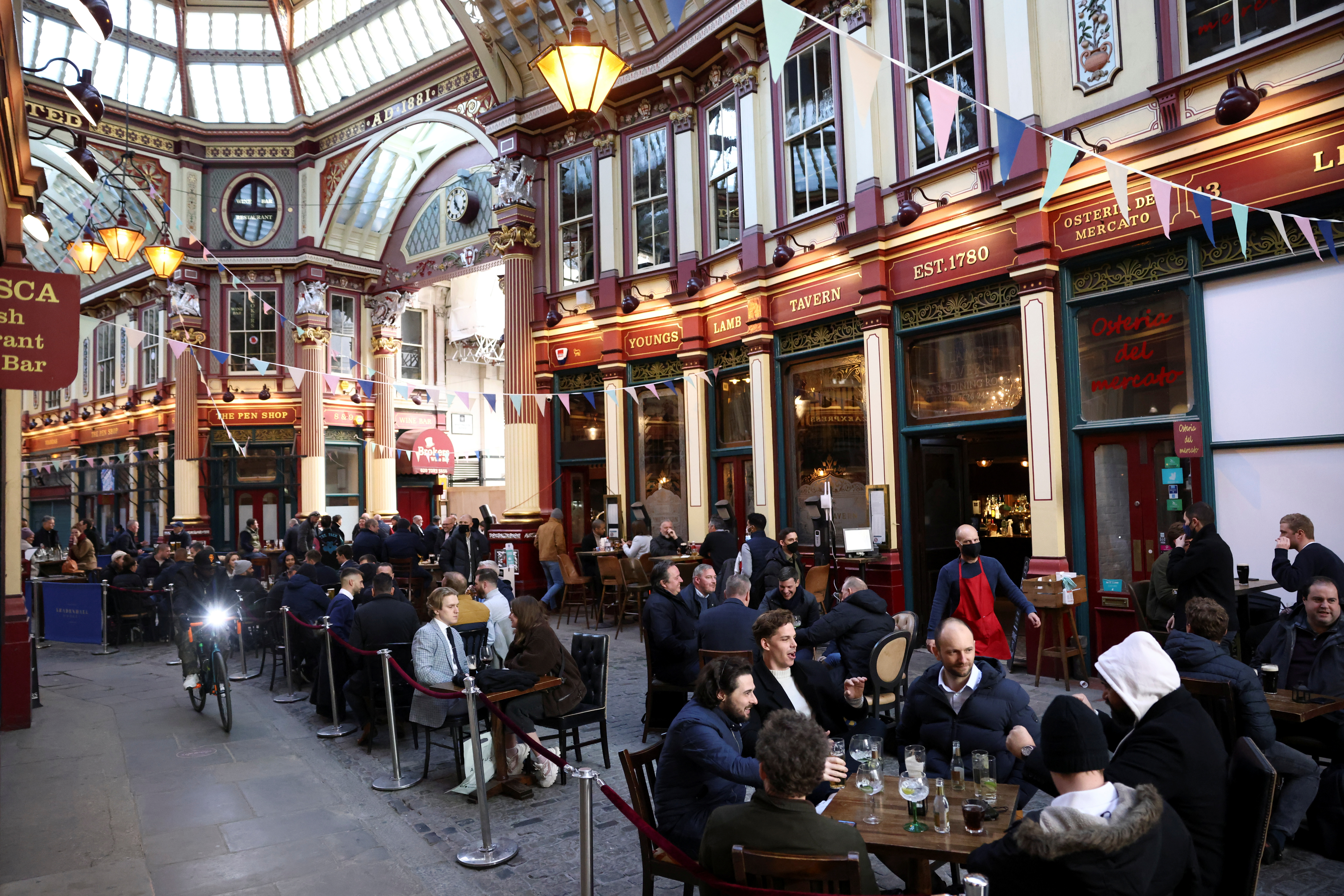 People sit at the terrace of a pub in Leadenhall market, as the coronavirus disease (COVID-19) restrictions ease, in London, Britain, April 16, 2021. REUTERS/Henry Nicholls