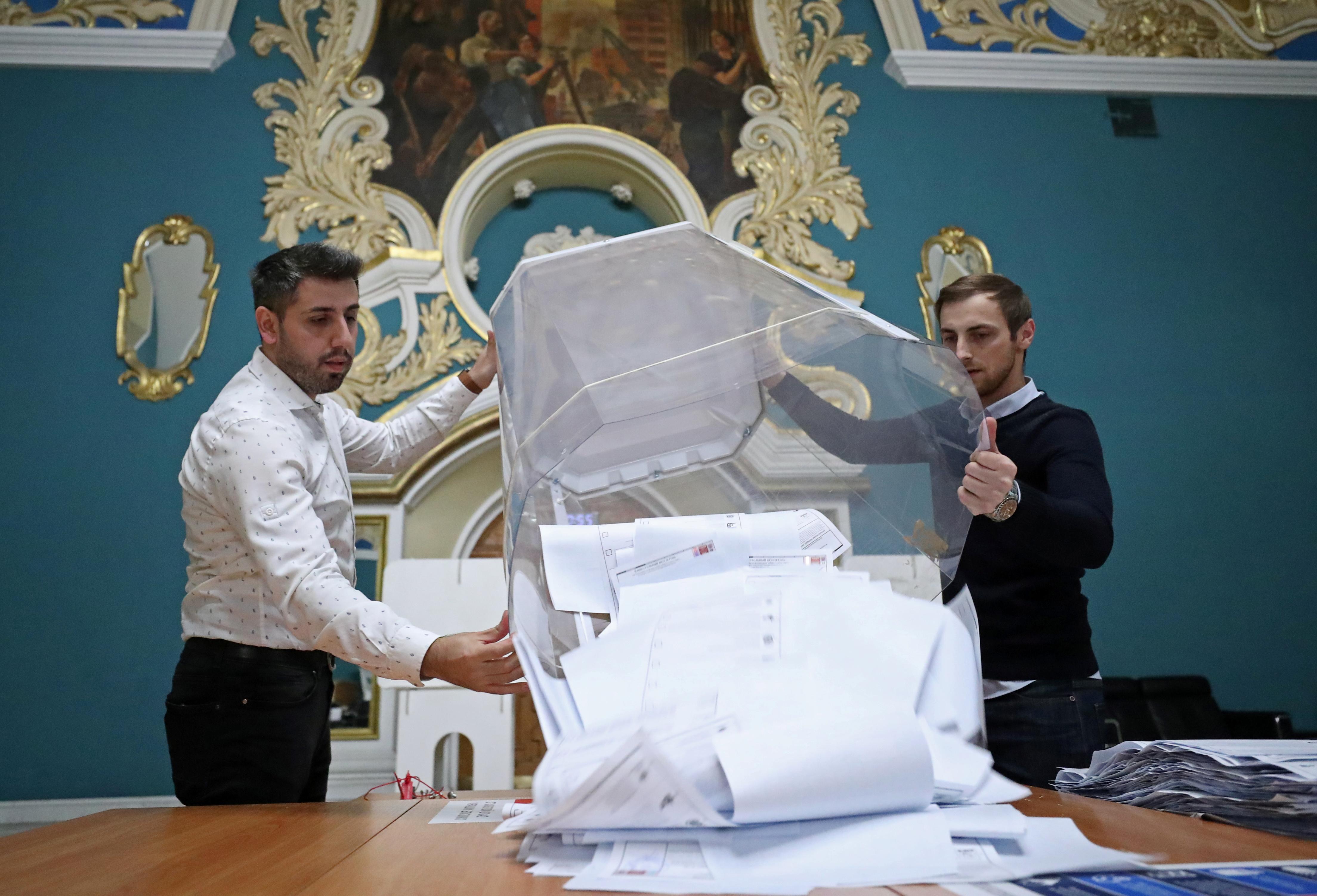 Lede van 'n plaaslike verkiesingskommissie maak 'n stembus leeg nadat stembusse gesluit is tydens 'n parlementsverkiesing van drie dae, by 'n stembus binne die Kazansky-treinstasie in Moskou, 19 September 2021. REUTERS/Evgenia Novozhenina