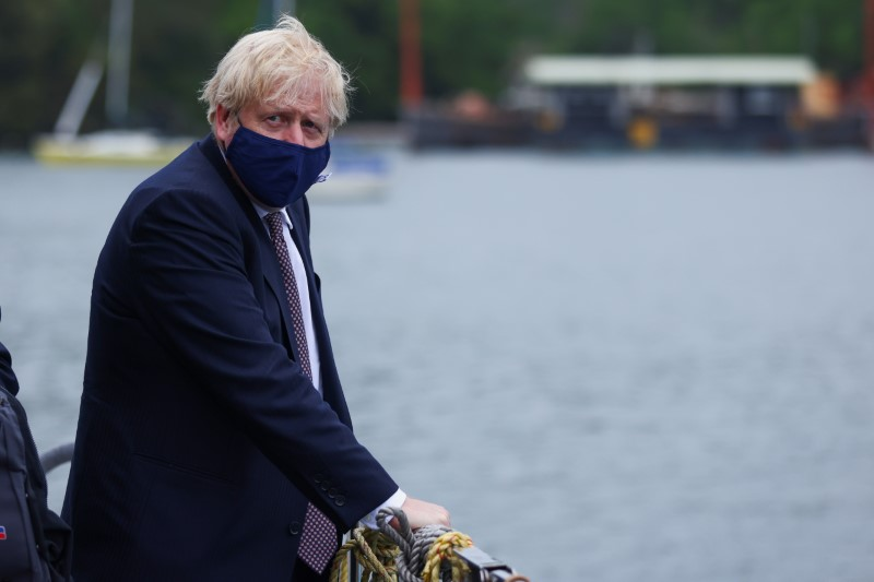 Britain's Prime Minister Boris Johnson arrives by boat to visit the workshop of Scott Woyka, ahead of the G7 summit, in Falmouth, Cornwall, Britain June 10, 2021. REUTERS/Tom Nicholson/Pool