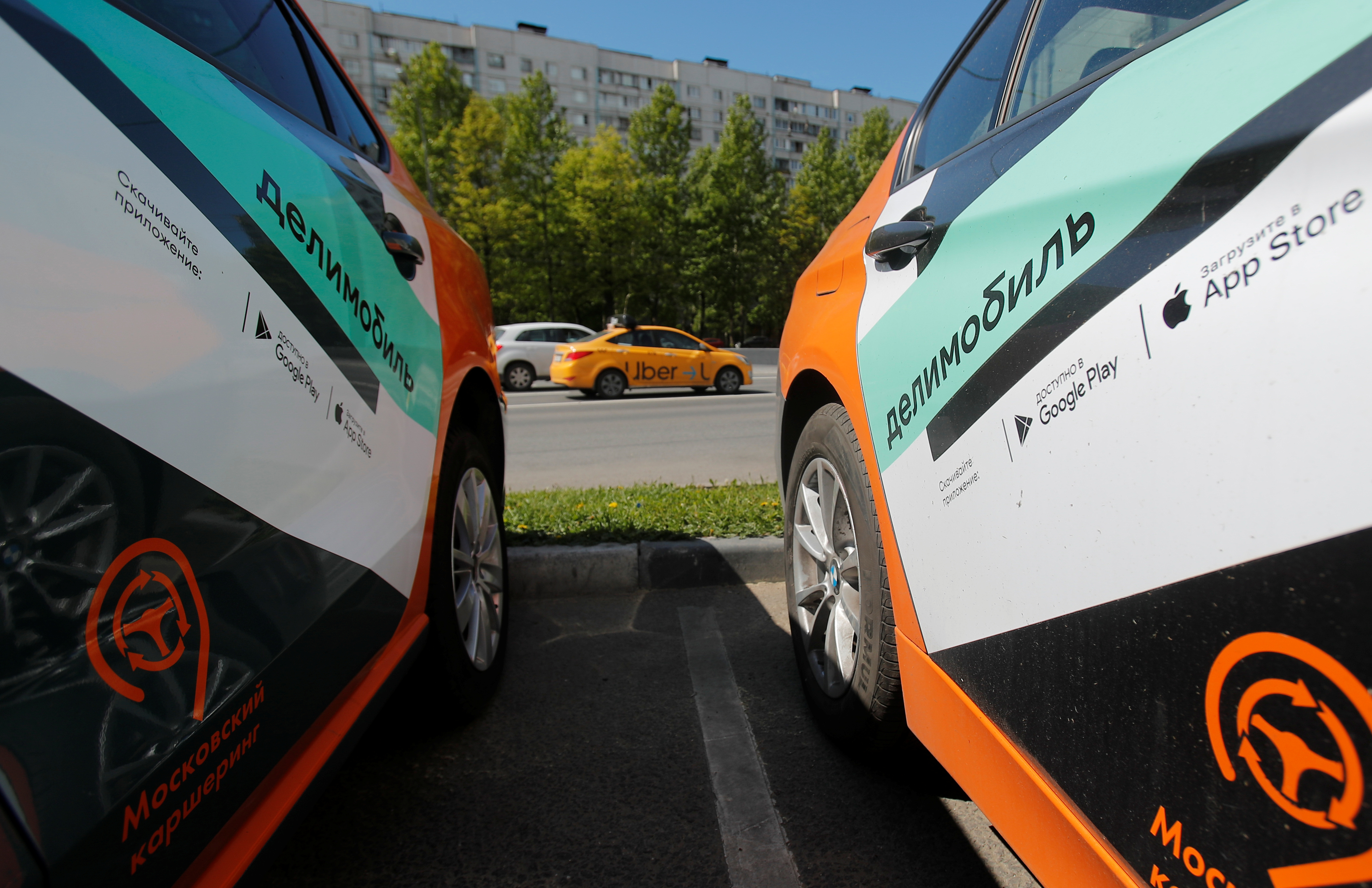 A taxi car drives by Delimobil branded vehicles amid the outbreak of the coronavirus disease (COVID-19) in Moscow, Russia May 20, 2020.  REUTERS/Maxim Shemetov