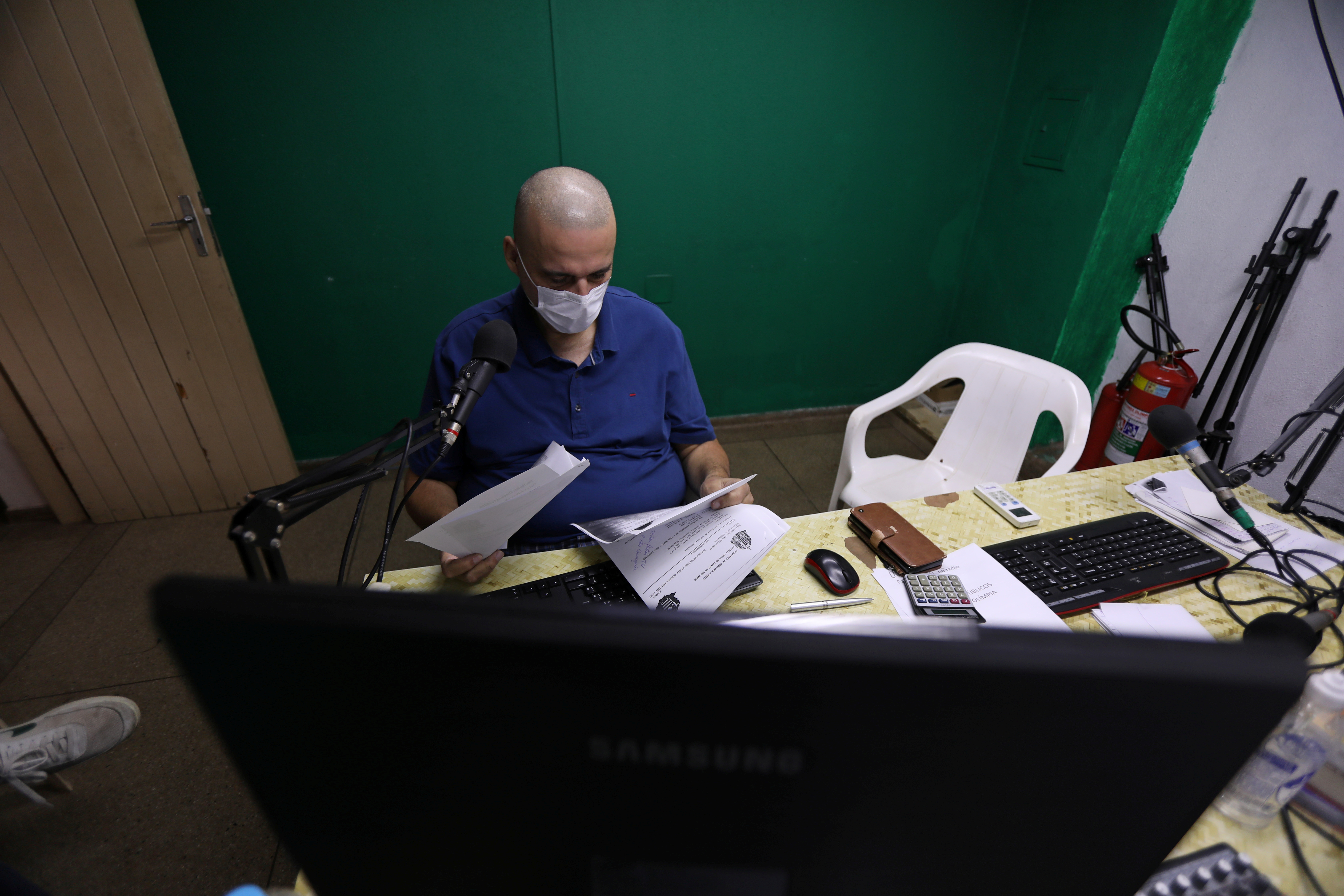 Jose Antonio Arantes, a local newspaper editor and radio host, who had his house been set on fire by a supporter of Brazil's President Jair Bolsonaro, is seen at his work desk amid the coronavirus disease (COVID-19) pandemic in Olimpia, Sao Paulo state, Brazil, June 9, 2021. REUTERS/Leonardo Benassatto