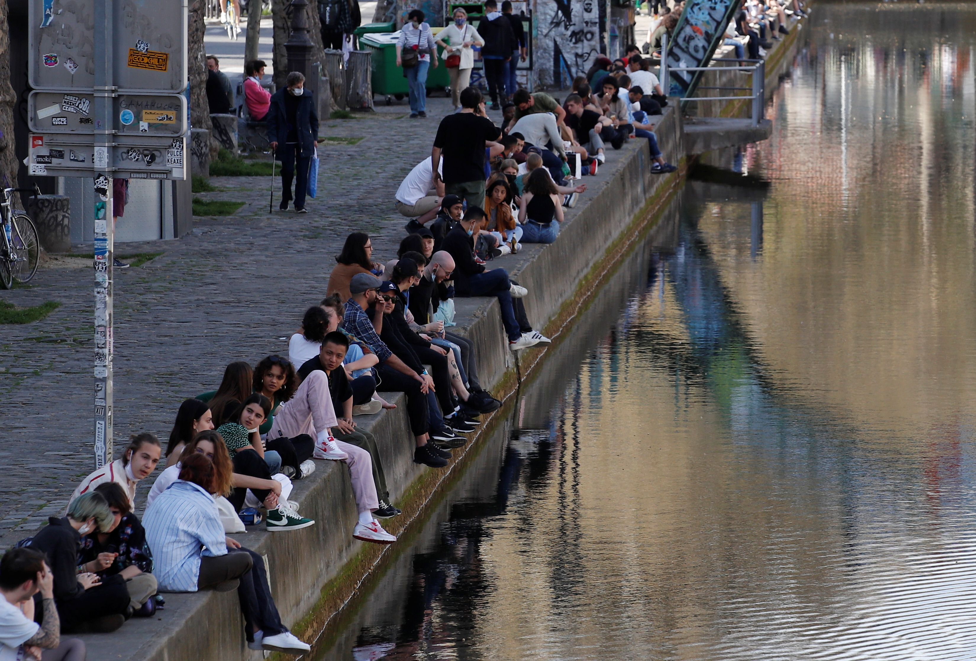 People enjoy a sunny and warm weather sitting along the Canal Saint-Martin in Paris amid the coronavirus disease (COVID-19) outbreak in France, March 31, 2021.  REUTERS/Gonzalo Fuentes