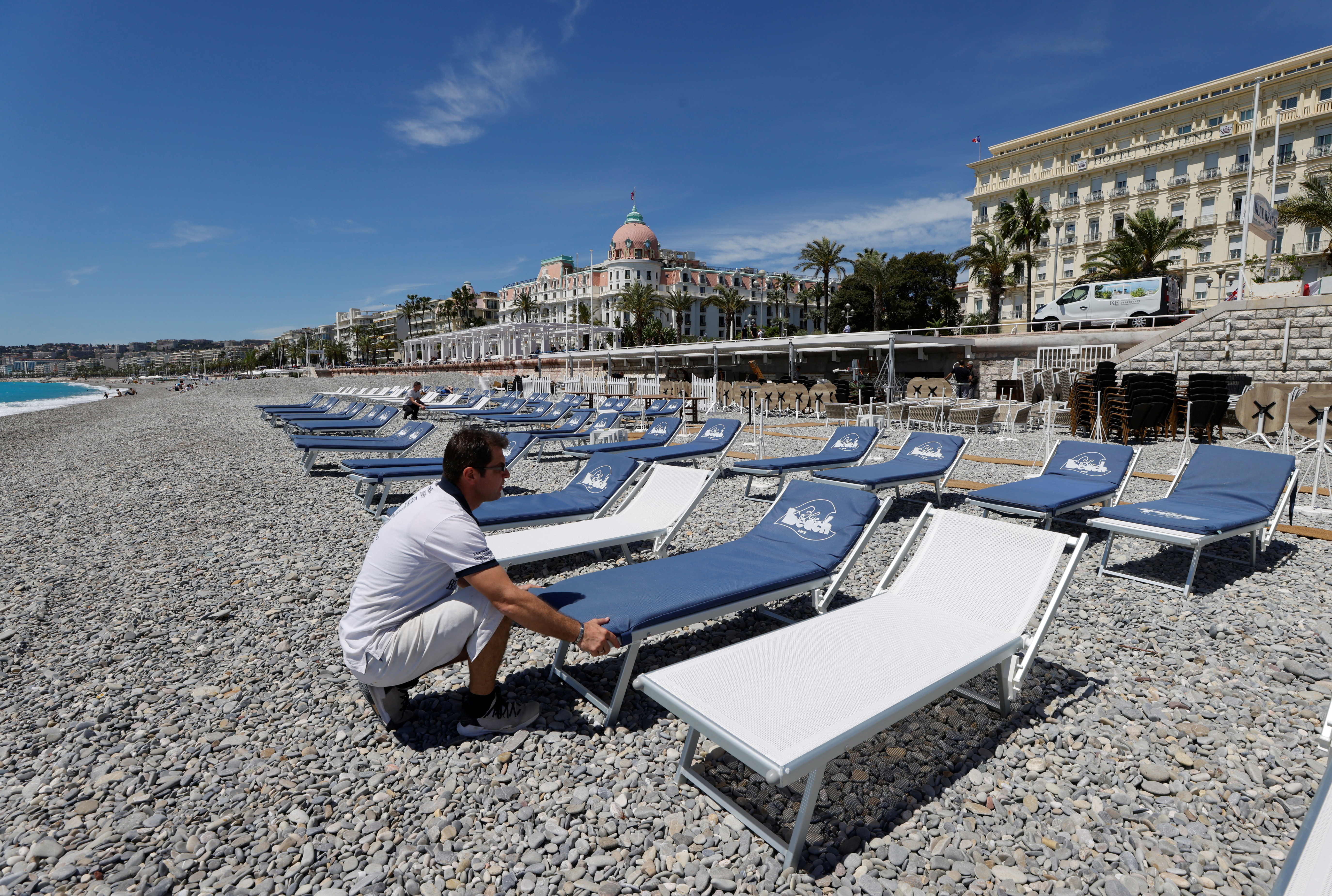 A beach worker installs mattresses on deckchairs during preparations for the reopenning of restaurants, bars and beaches in Nice as part of an easing of the country's lockdown restrictions amid the coronavirus disease (COVID-19) outbreak in France, May 17, 2021. REUTERS/Eric Gaillard