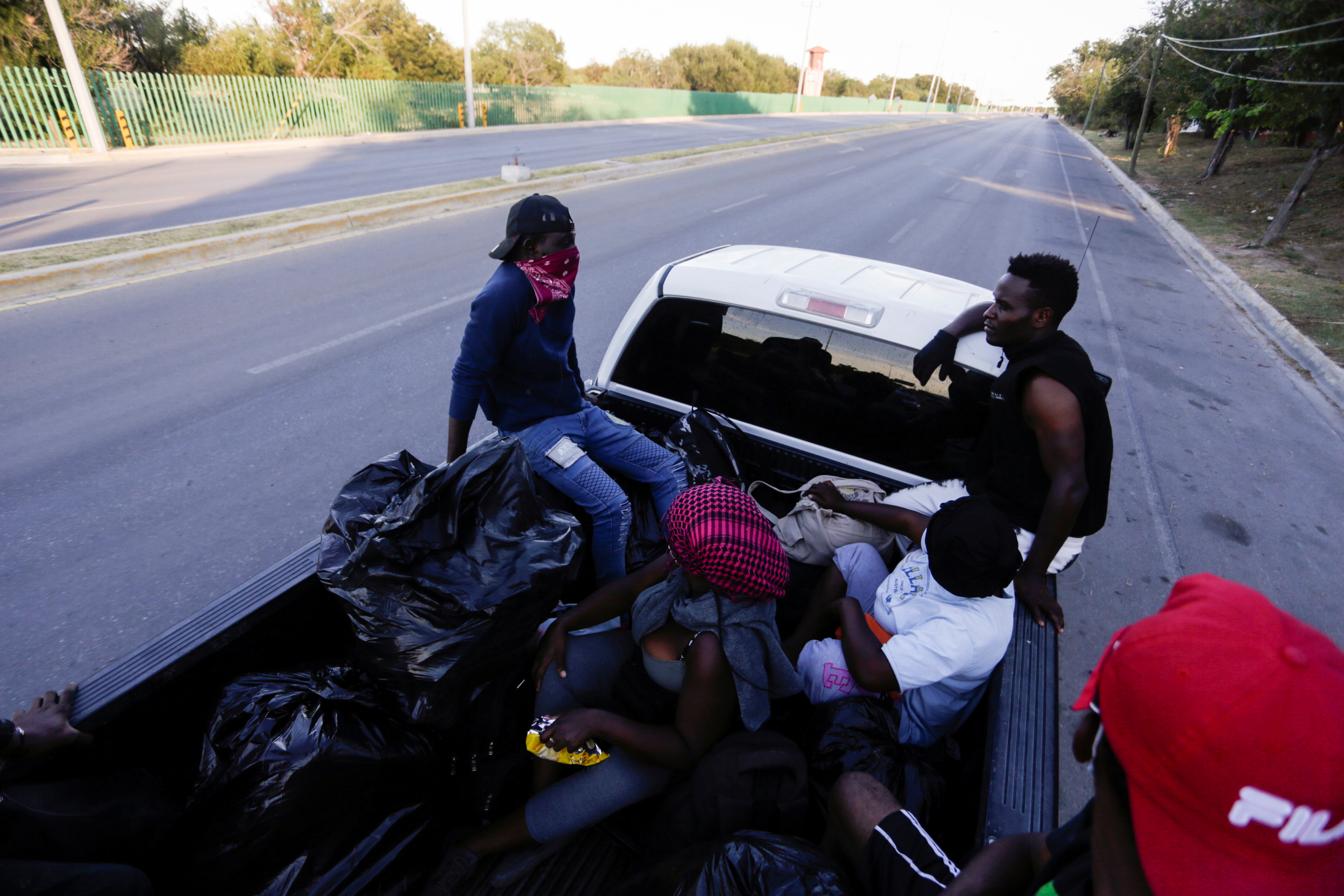 Migrants are driven to a fixed shelter from a makeshift camp near the border with the U.S., in Ciudad Acuna, Mexico, September 24, 2021. REUTERS/Daniel Becerril