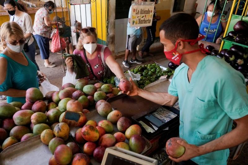 People buy mangos in a public market in Havana, Cuba, June 12, 2021. Picture taken on June 12, 2021. REUTERS/Alexandre Meneghini