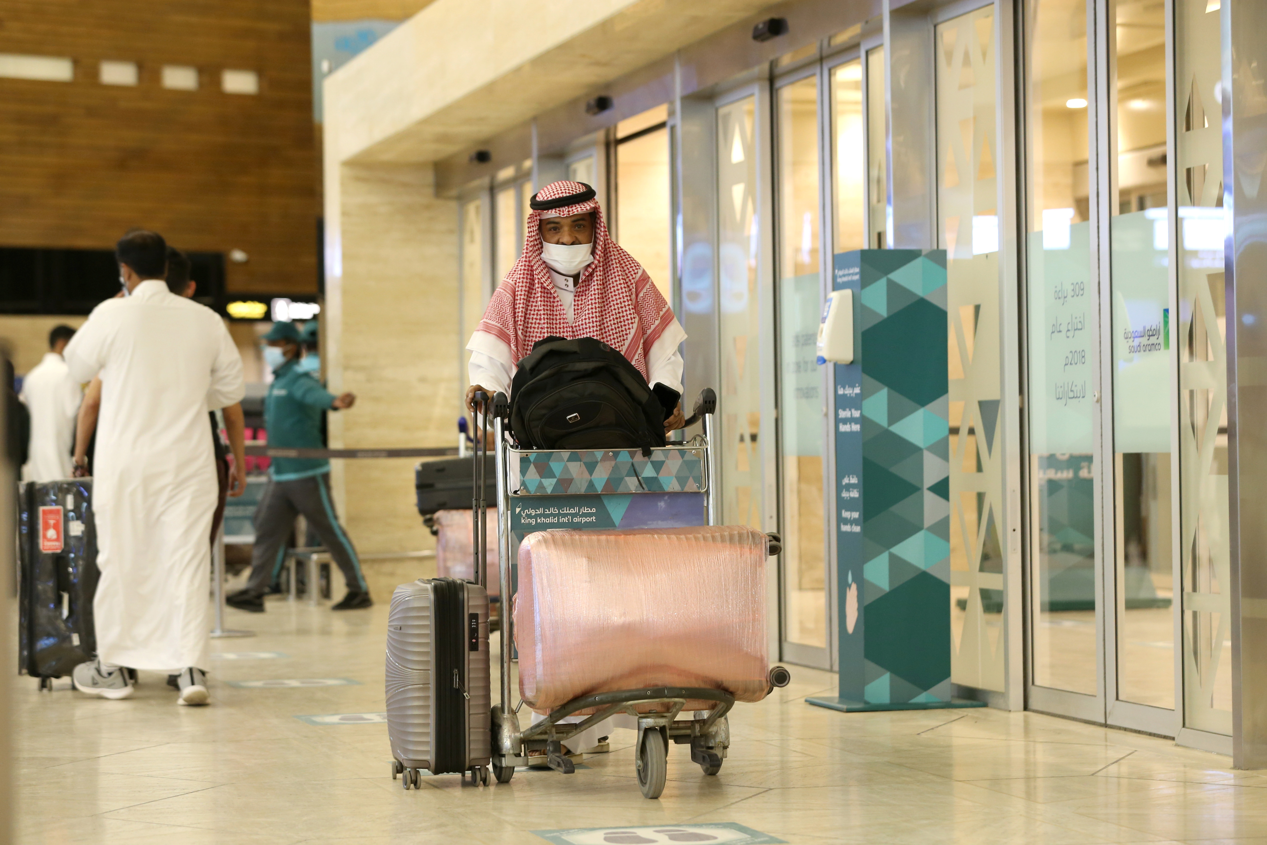 A Saudi man wearing a face mask is seen with his luggage as he arrives at the King Khalid International Airport, after Saudi authorities lift the travel ban on its citizens after fourteen months due to Coronavirus (COVID-19) restrictions, in Riyadh, Saudi Arabia, May 16, 2021. REUTERS/Ahmed Yosri/Files