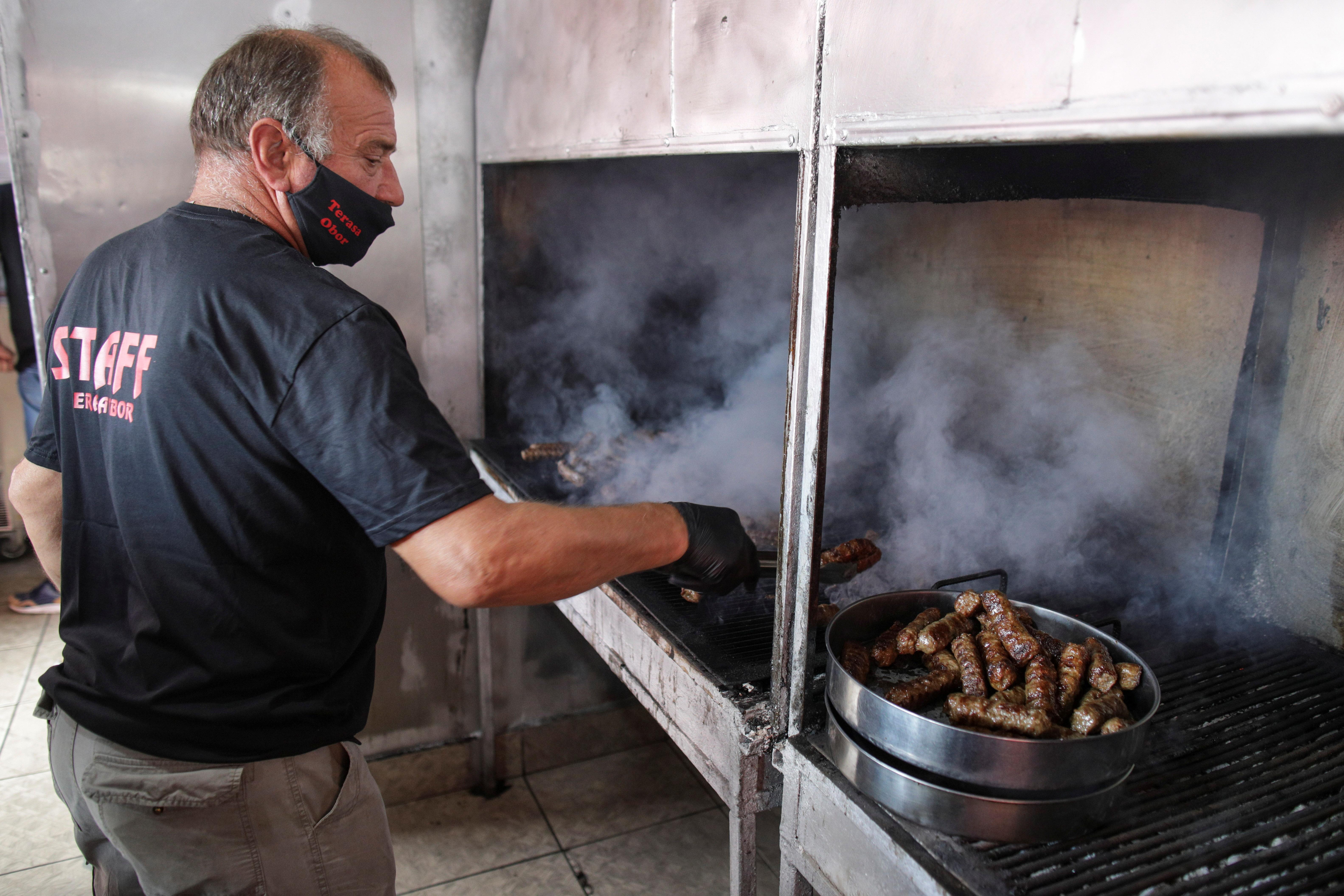 A man grills traditional Romanian minced meat rolls called 'mici' in Bucharest, Romania, June 11, 2021. Inquam Photos/Octav Ganea via REUTERS