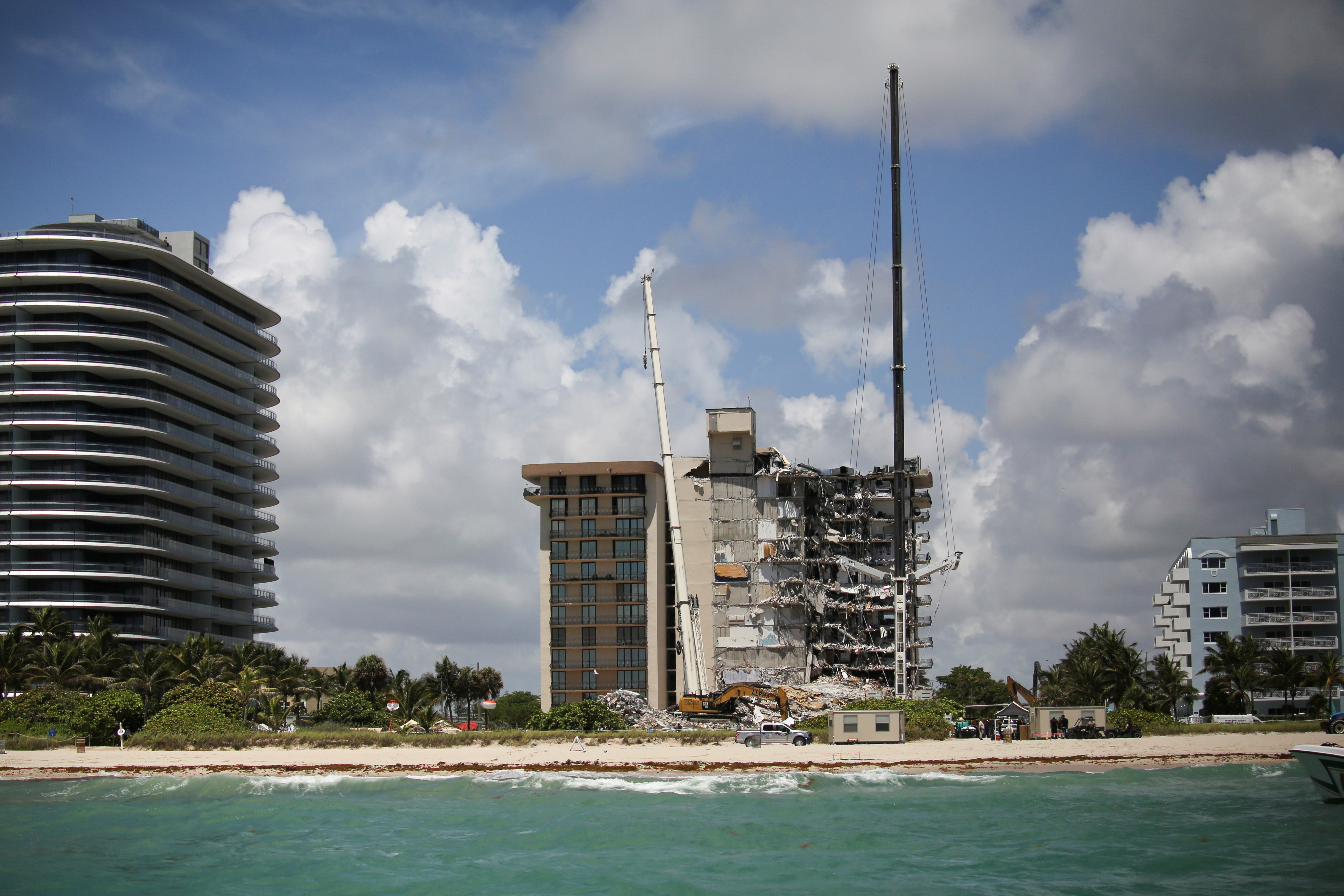A general view of a partially collapsed residential building as the emergency crews continue search and rescue operations for survivors, in Surfside, near Miami Beach, Florida, U.S. June 27, 2021. REUTERS/Marco Bello