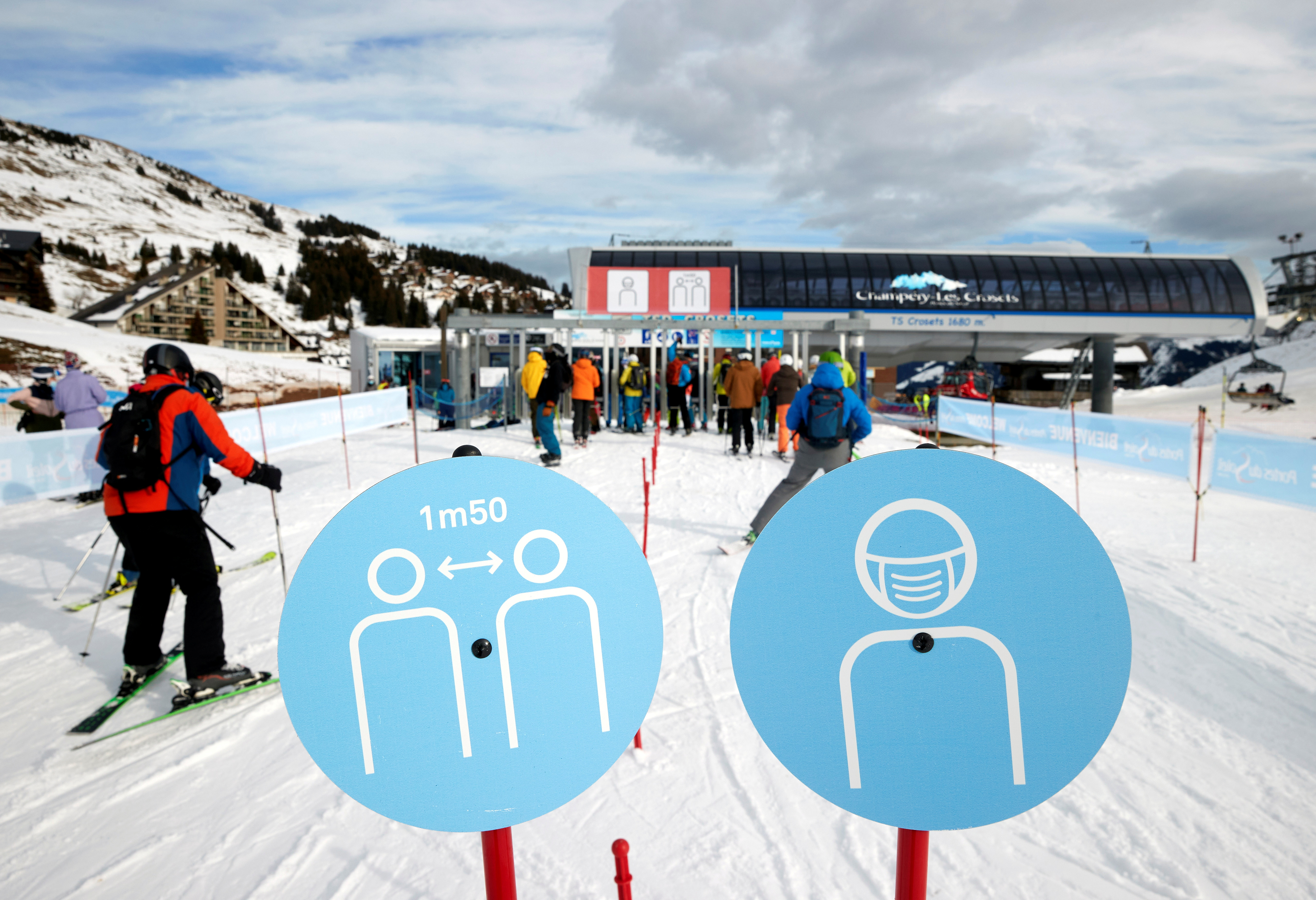 Skiers pass the restriction signs to line up at the chairlift at Les Portes du Soleil ski resort during the global outbreak of the coronavirus disease (COVID-19), in Les Crosets, Switzerland, December 19, 2020. REUTERS/Denis Balibouse