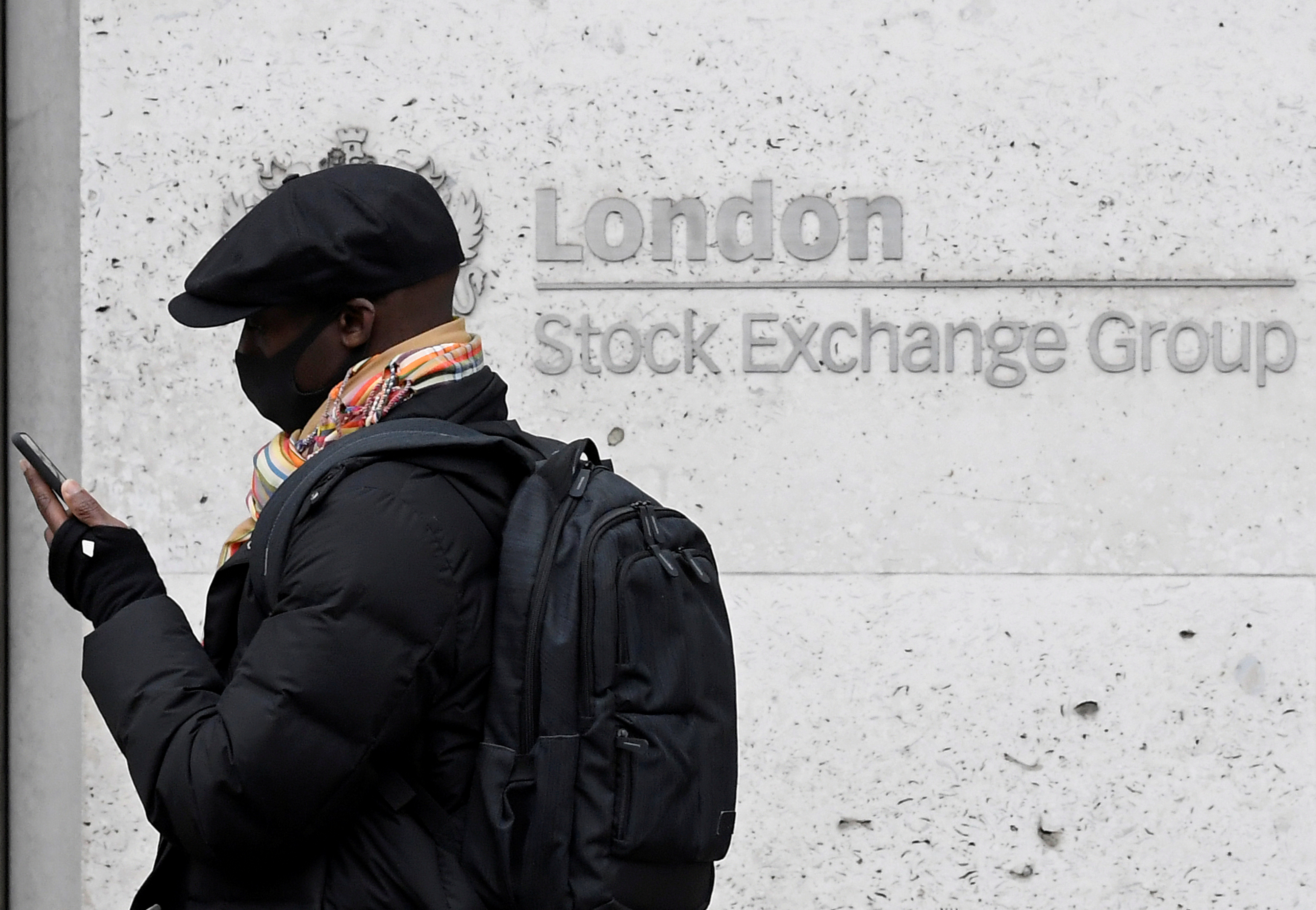 A man wearing a protective face mask walks past the London Stock Exchange Group building in the City of London financial district, whilst British stocks tumble as investors fear that the coronavirus outbreak could stall the global economy, in London, Britain, March 9, 2020. REUTERS/Toby Melville/File Photo