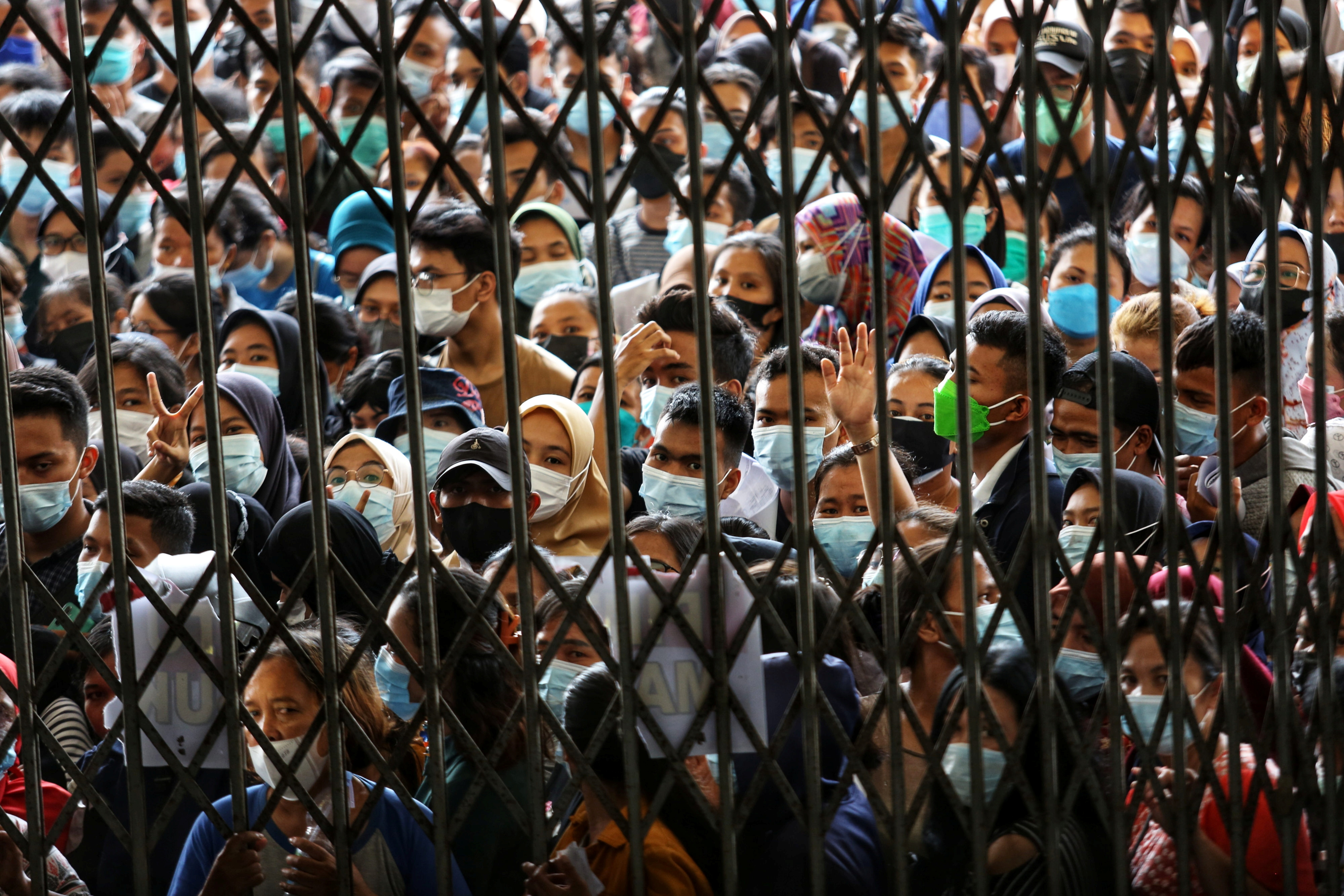 People wearing protective face masks stand in line wait to receiving a dose of the vaccine against the coronavirus disease (COVID-19), during a vaccination program at the provincial government building in Medan, North Sumatra province, Indonesia August 3, 2021, Picture taken August 3, 2021. Antara Foto/Fransisco Carolio/via Reuters