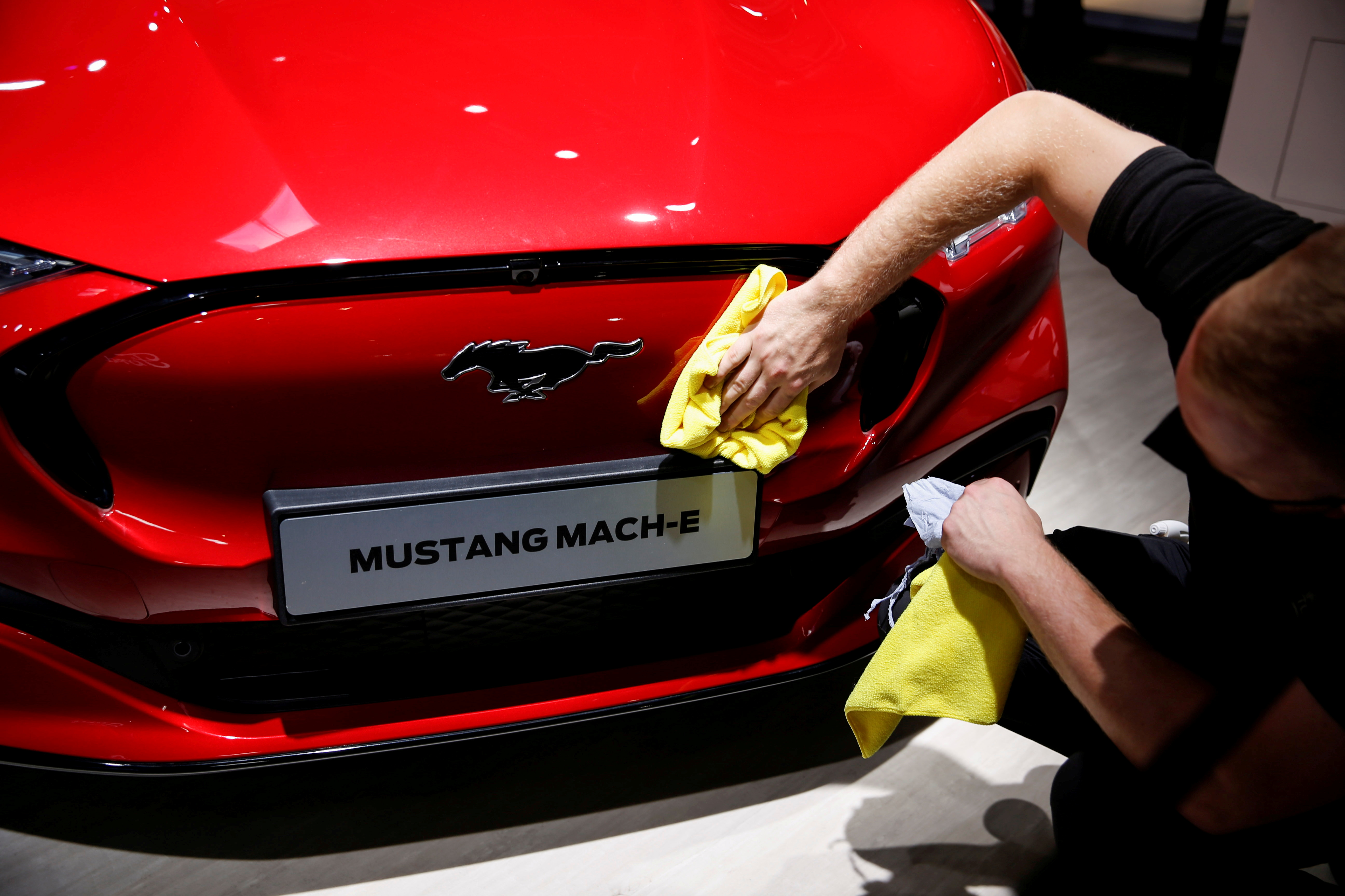 A worker prepares Ford Mustang Mach-E ahead of the Munich Motor Show IAA Mobility 2021 in Munich, Germany, September 6, 2021. REUTERS/Michaela Rehle