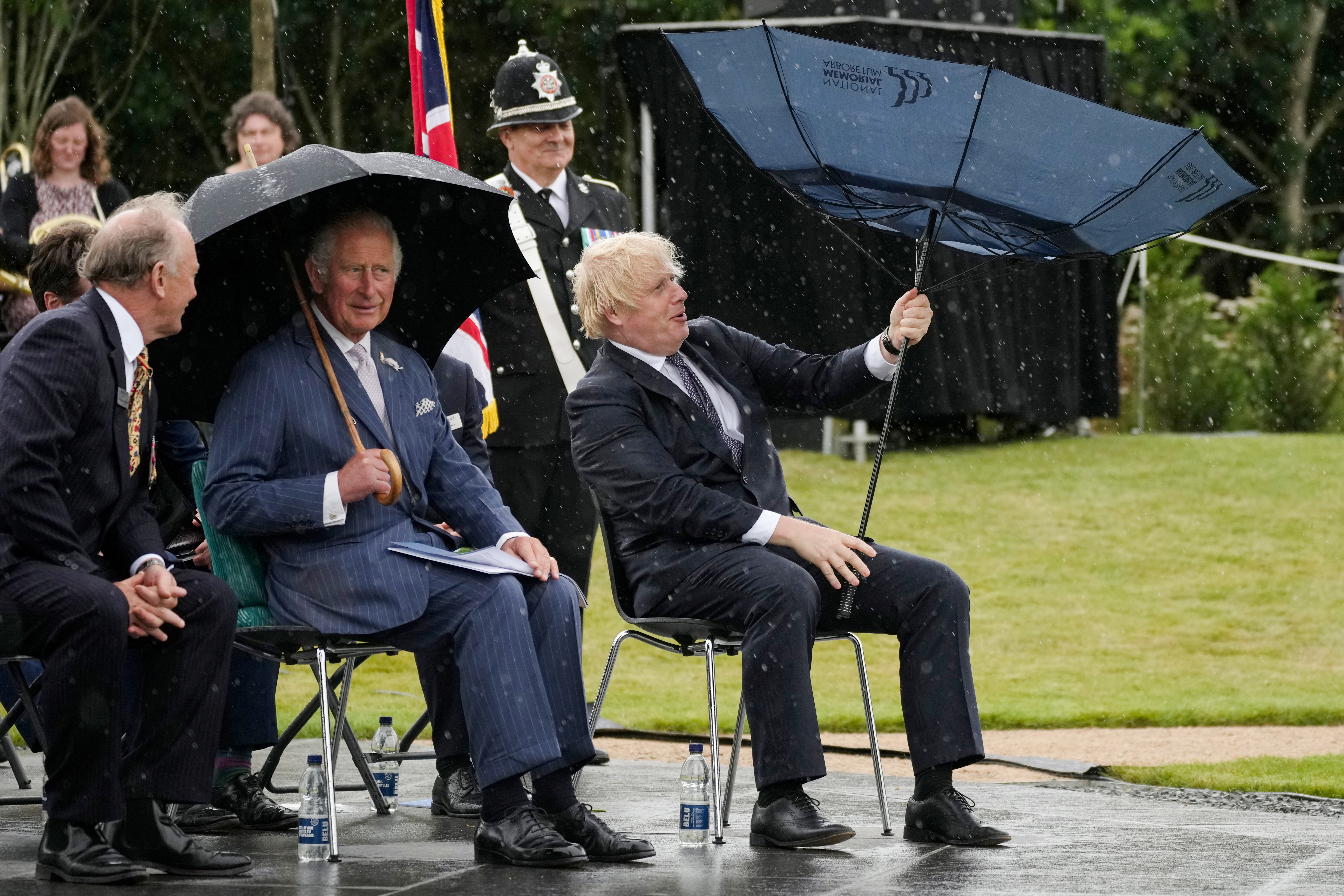 Britain's Prince Charles looks on as Prime Minister Boris Johnson opens his umbrella at the National Memorial Arboretum in Staffordshire, Britain July 28, 2021. Christopher Furlong/Pool via REUTERS