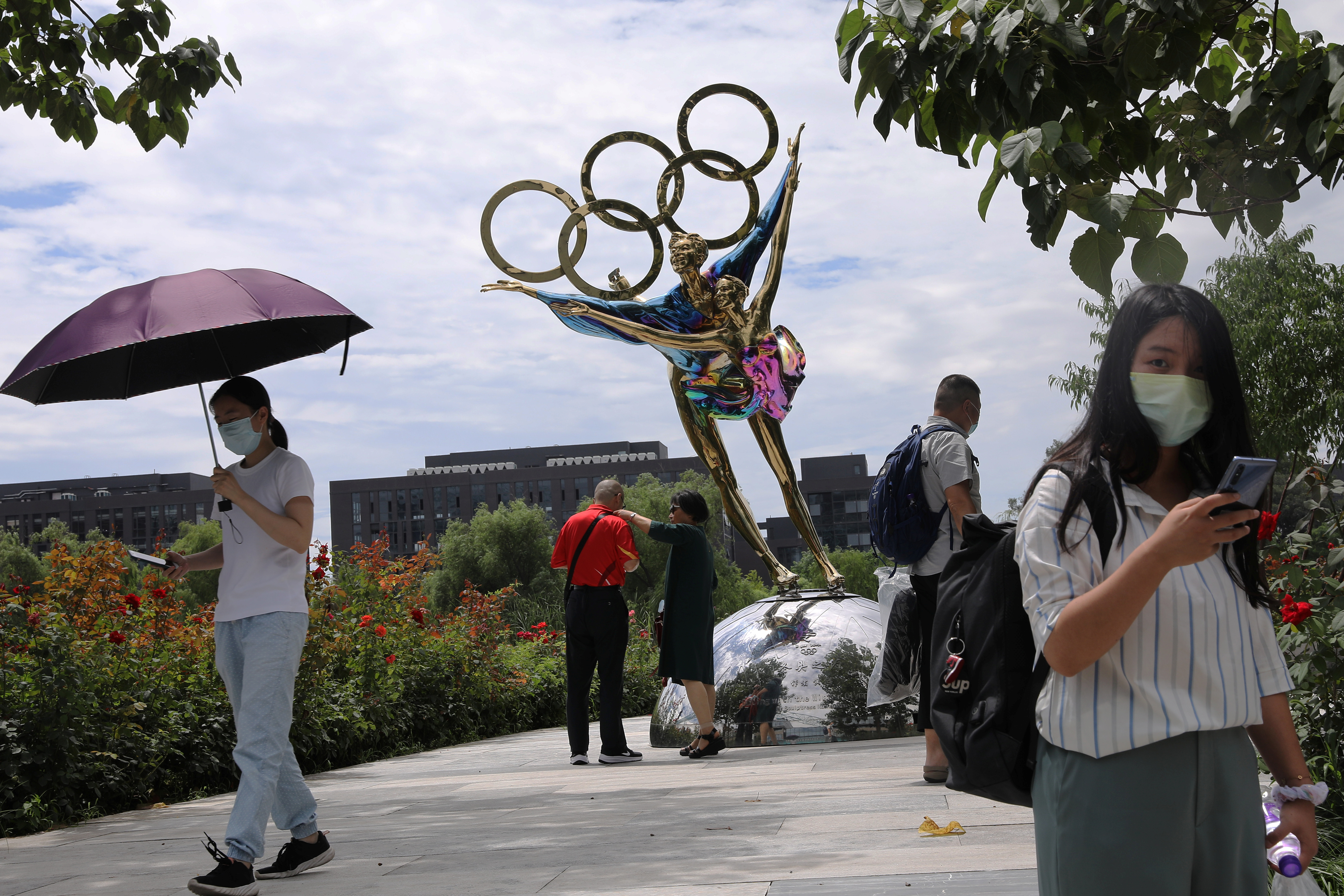 Visitors are seen next to a sculpture featuring skates outside the headquarters of Beijing Organising Committee for the Beijing 2022 Olympic and Paralympic Winter Games in Beijing, China July 30, 2021. REUTERS/Tingshu Wang