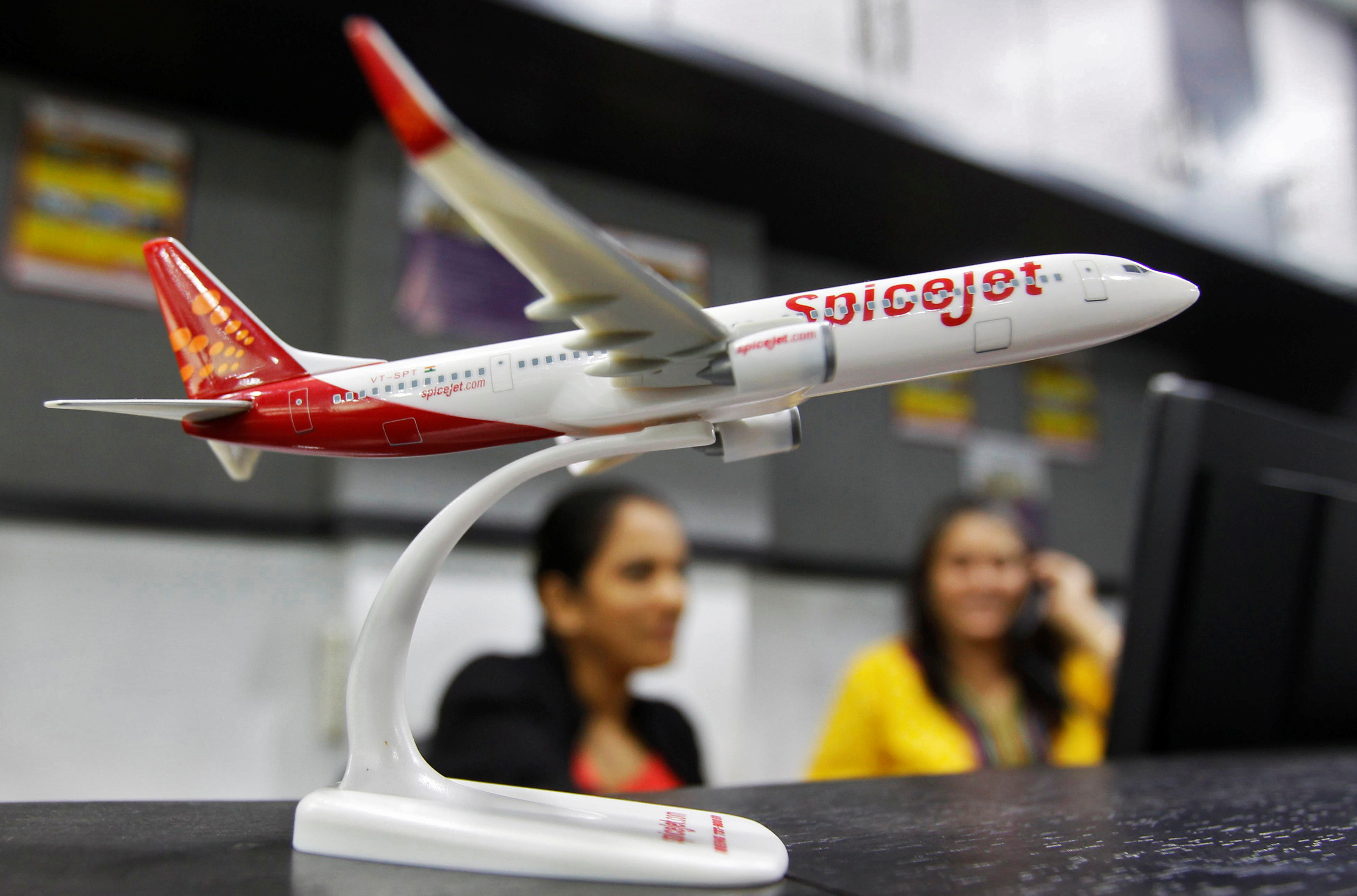 Employees work inside a travel agency office beside a model of a SpiceJet aircraft in the western Indian city of Ahmedabad February 14, 2014. REUTERS/Amit Dave/File Photo