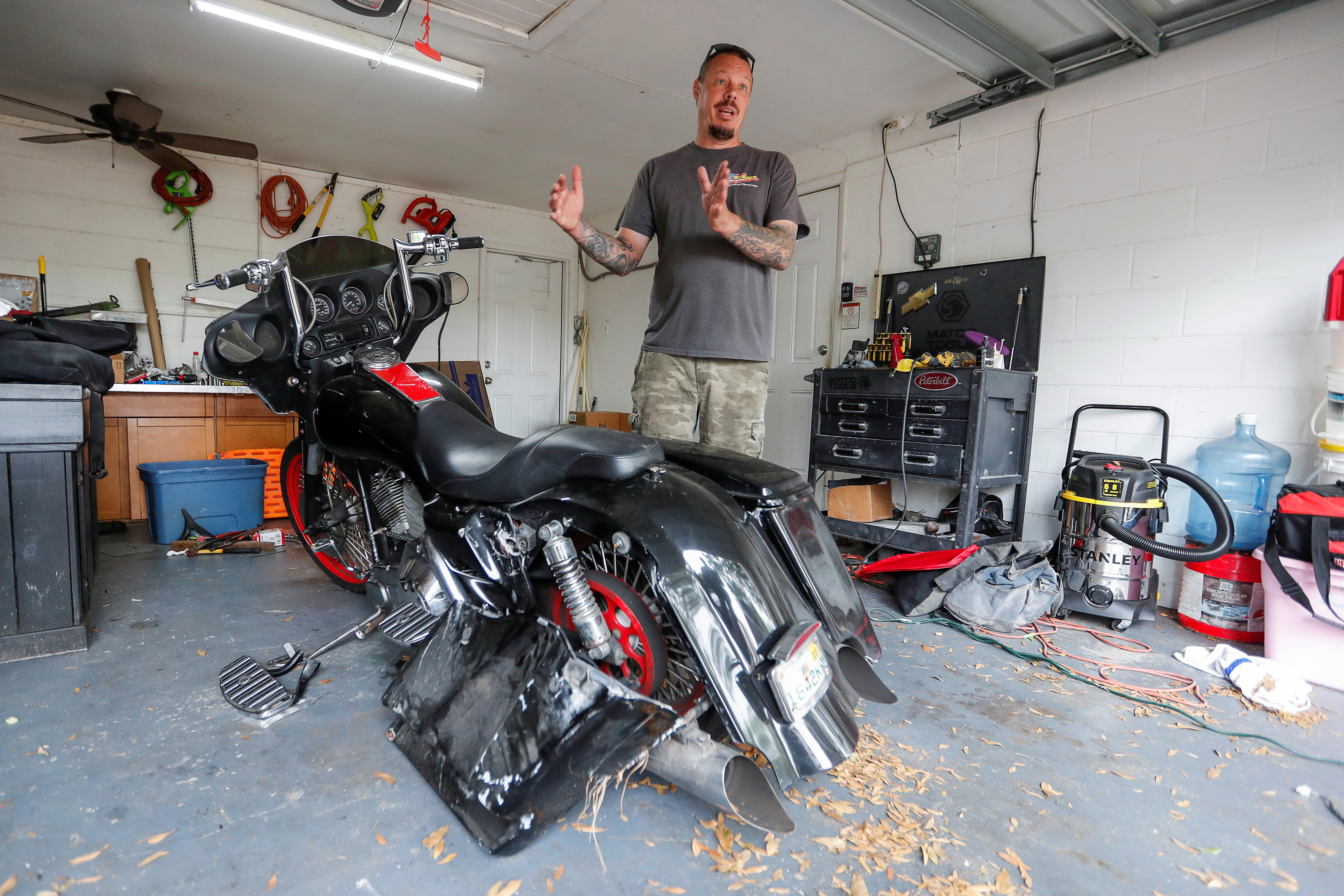 Jesse Ohlau stands next to his wrecked motorcycle as he speaks with Reuters at his home in Brandon, Florida, U.S., March 29, 2021. Picture taken March 29, 2021.  REUTERS/Joe Skipper