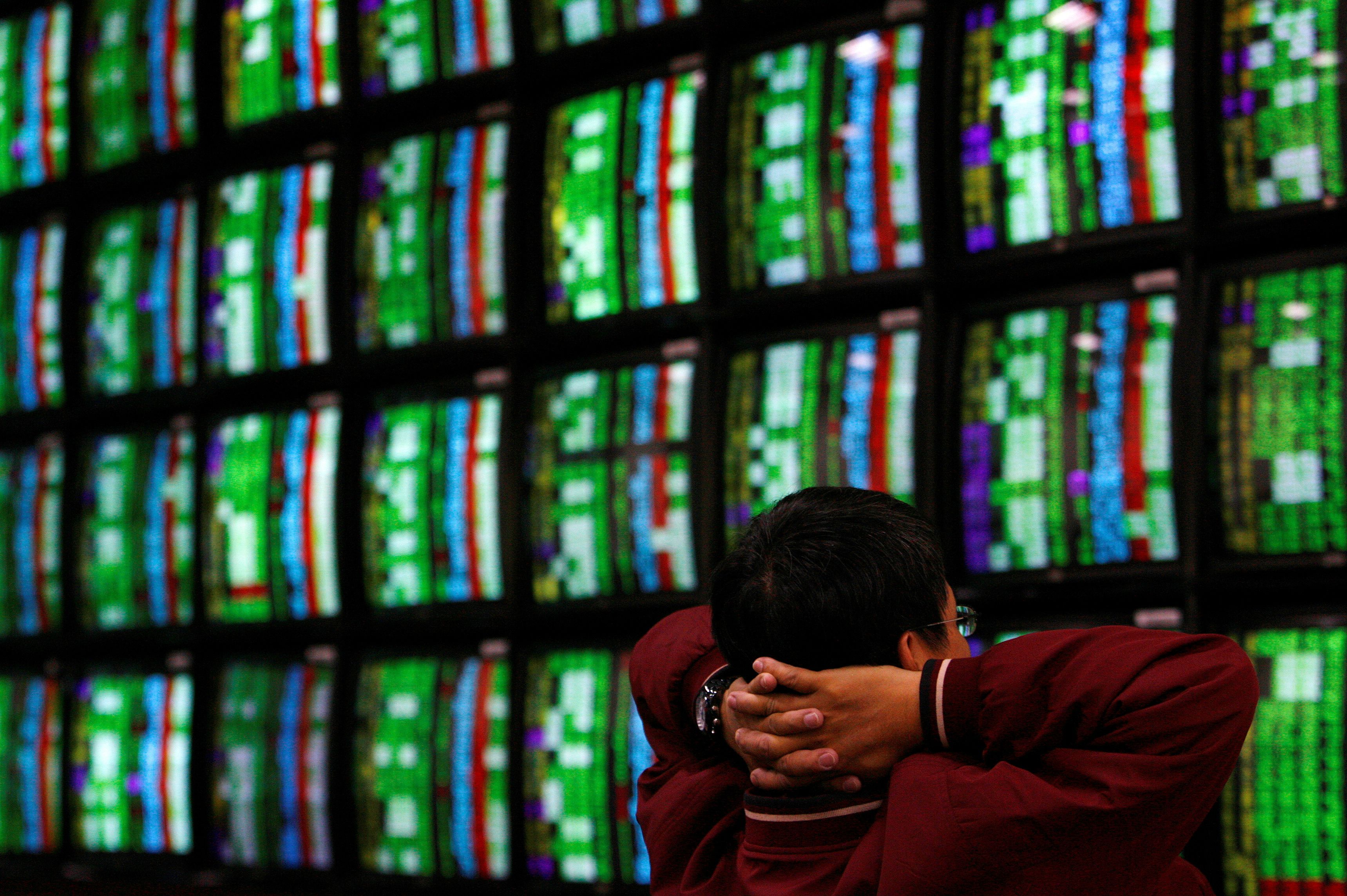 A man looks at stock market monitors in Taipei January 22, 2008. REUTERS/Nicky Loh/File Photo