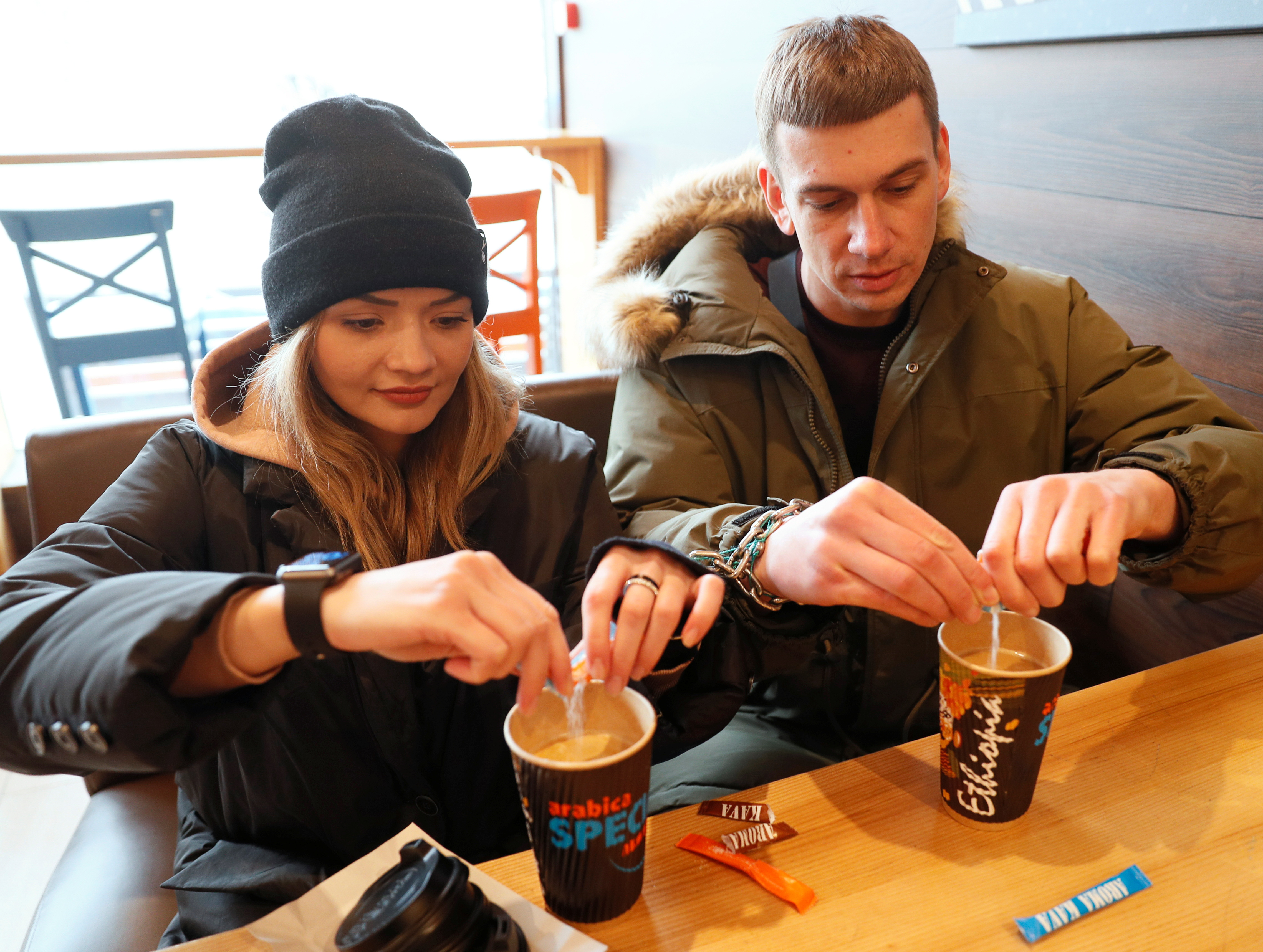 Alexandr Kudlay, 33, and Viktoria Pustovitova, 28, drink coffee in a cafe in Kharkiv, Ukraine March 5, 2021. Tired of occasional break-ups, this Ukrainian couple found an unusual solution to stay inseparable. On St. Valentine's Day, they decided to handcuff their hands together for three months and began documenting their experience on social media. Picture taken March 5, 2021.  REUTERS/Gleb Garanich/File Photo