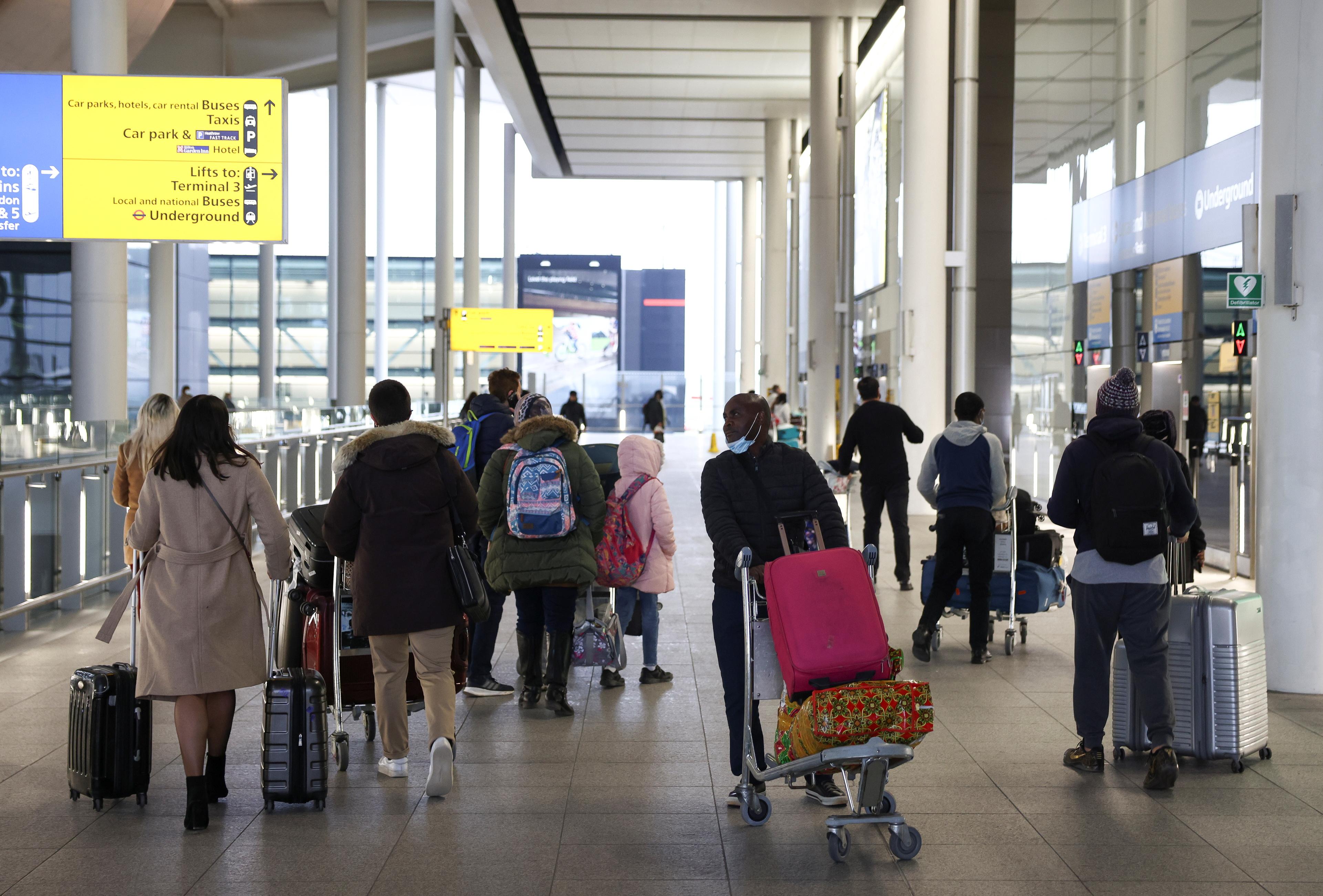 Travellers walk through Terminal 2 at Heathrow Airport, amid the coronavirus disease (COVID-19) outbreak in London, Britain February 14, 2021. REUTERS/Henry Nicholls