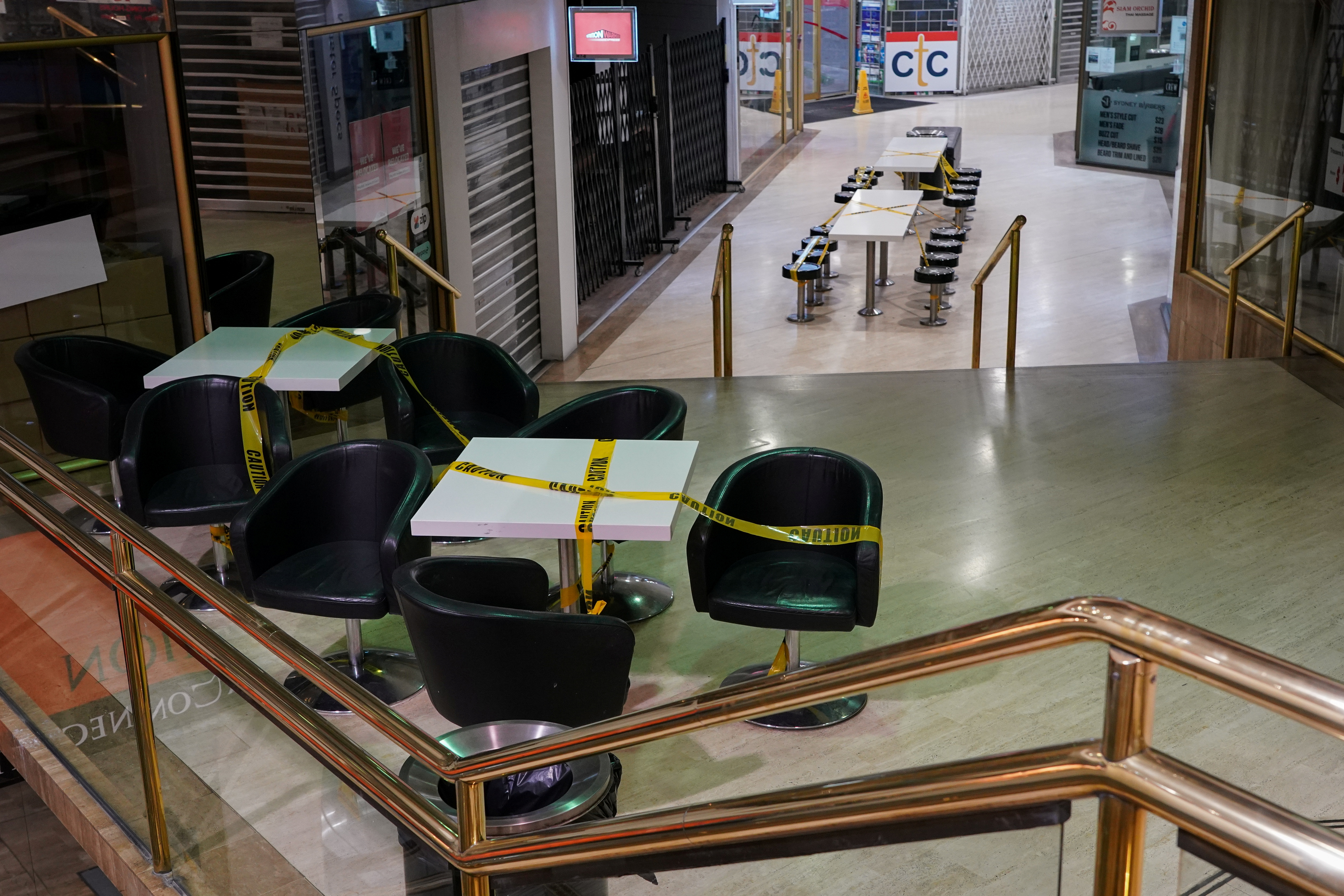 Tables marked with caution tape to prevent people from sitting are seen in an empty city centre mall during a lockdown to curb the spread of a coronavirus disease (COVID-19) outbreak in Sydney, Australia, July 28, 2021.  REUTERS/Loren Elliott