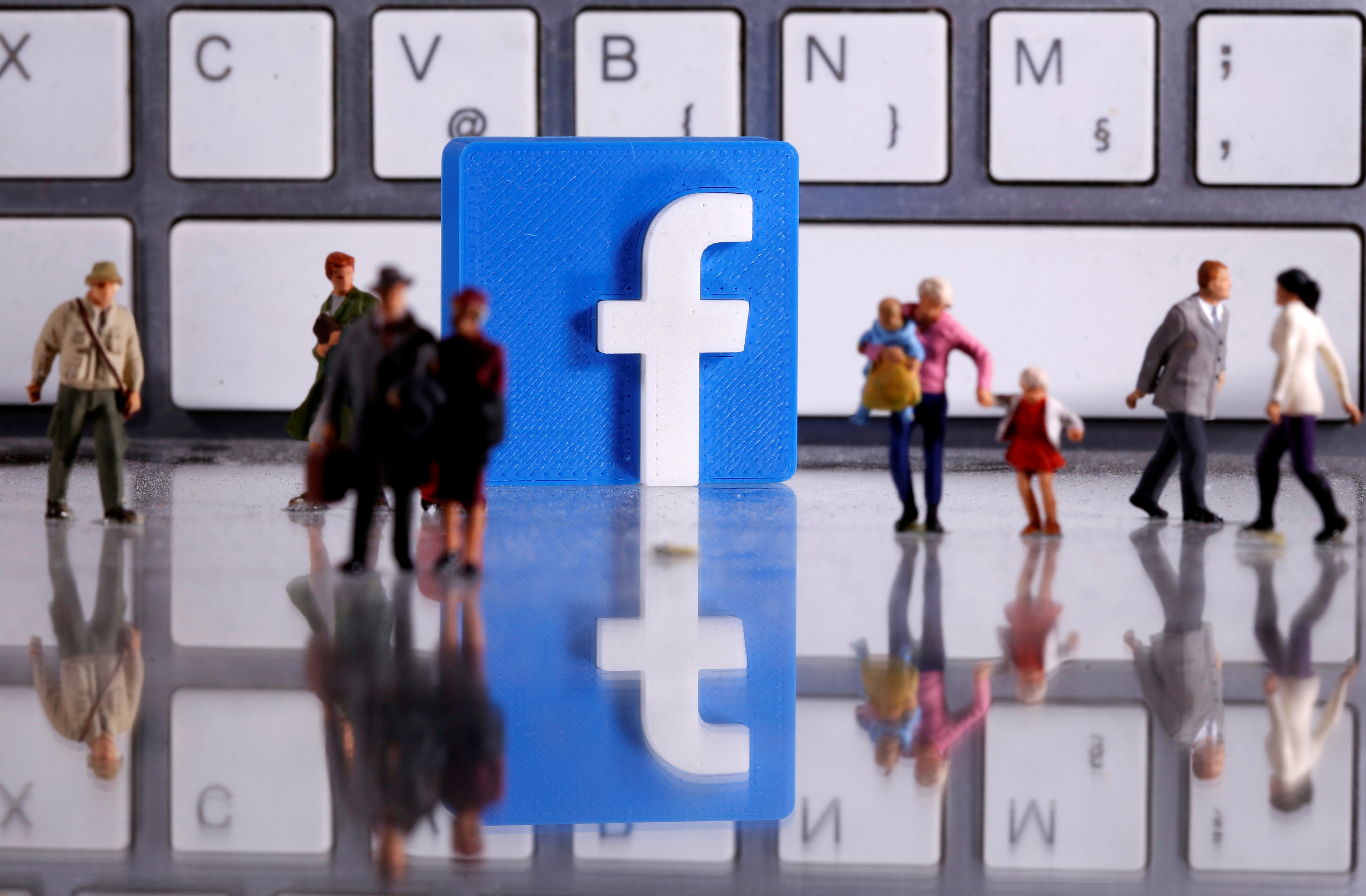 A 3D printed Facebook logo is placed between small toy people figures in front of a keyboard in this illustration taken April 12, 2020. REUTERS/Dado Ruvic/Illustration