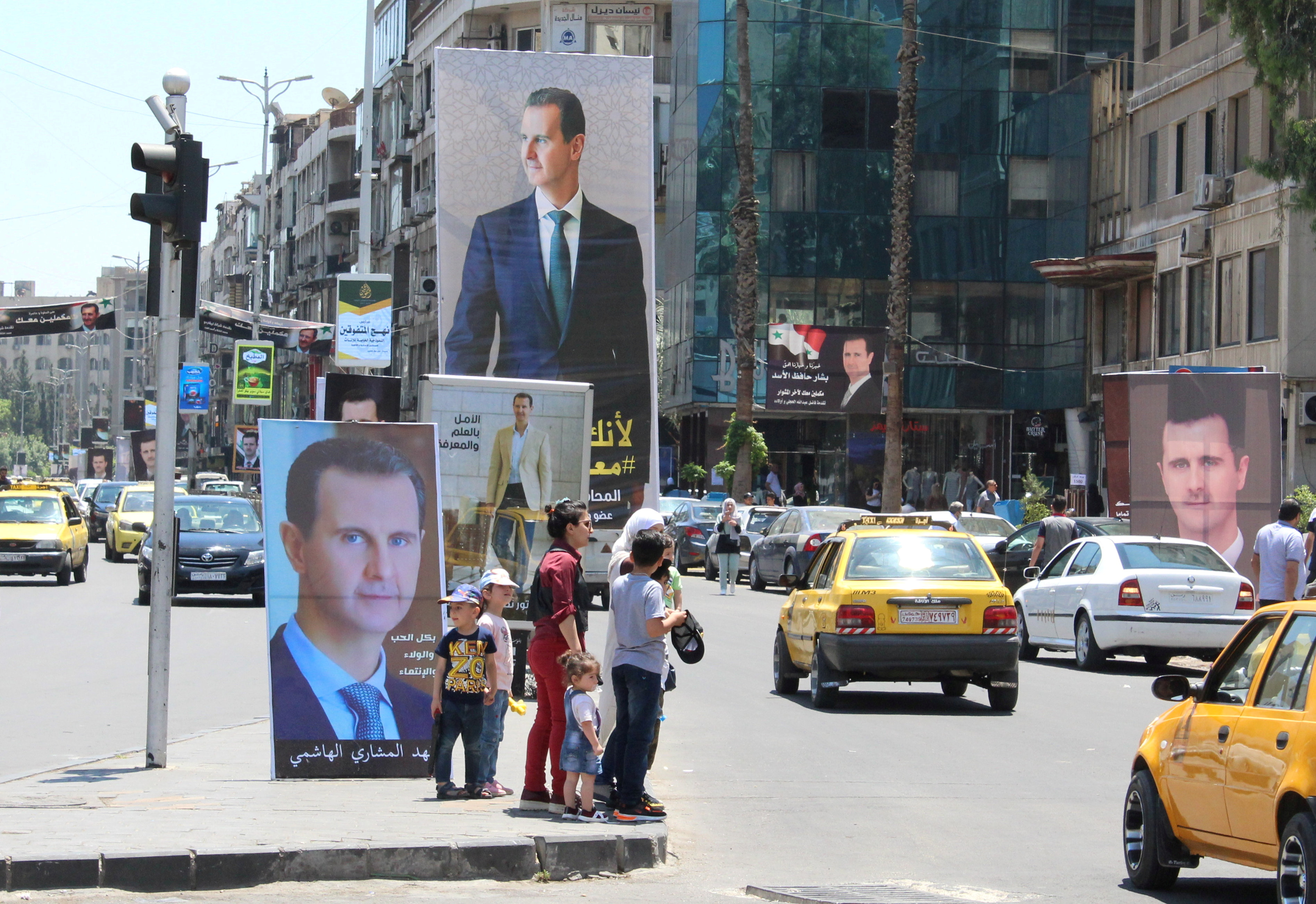 People stand near posters depicting Syria's President Bashar al-Assad, ahead of the May 26 presidential election, in Damascus, Syria May 18, 2021.  REUTERS/Firas Makdesi/File Photo