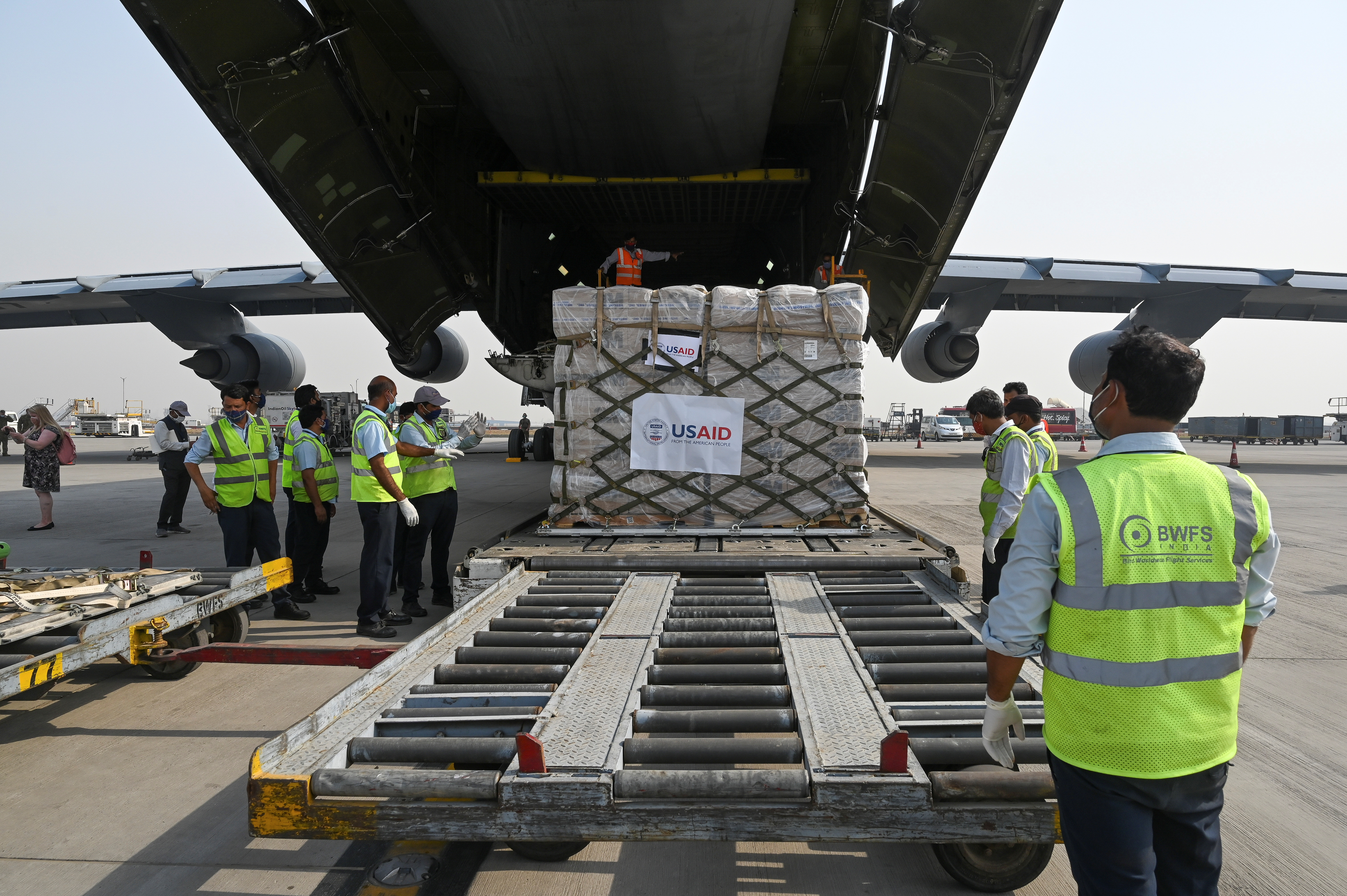 Ground staff unload coronavirus disease (COVID-19) relief supplies from the United States at the Indira Gandhi International Airport cargo terminal in New Delhi, India April 30, 2021. Prakash Singh/Pool via REUTERS