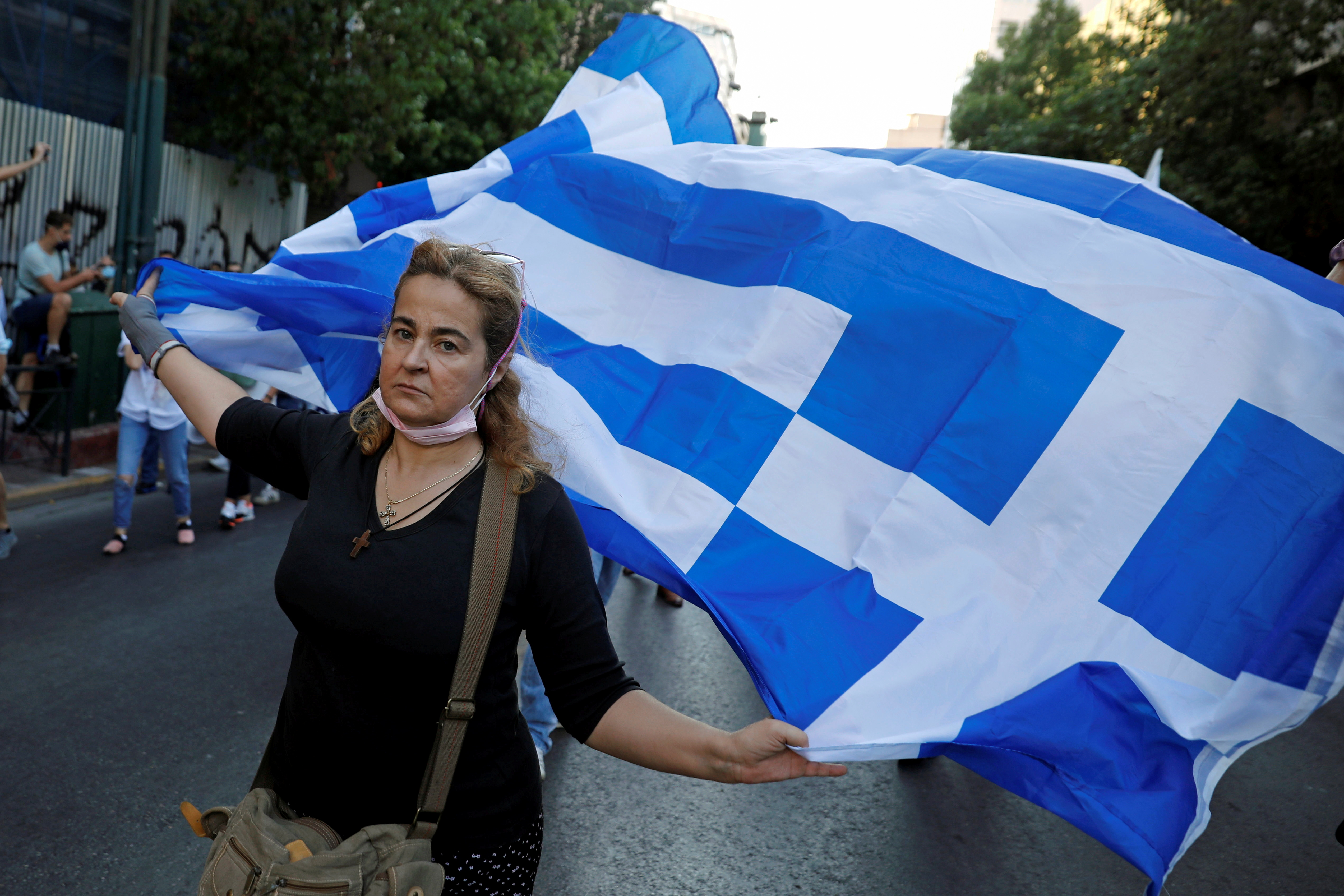 An anti-vaccine demonstrator holds a Greek flag during a protest against coronavirus disease (COVID-19) vaccinations, in Athens, Greece, July 24, 2021. REUTERS/Costas Baltas